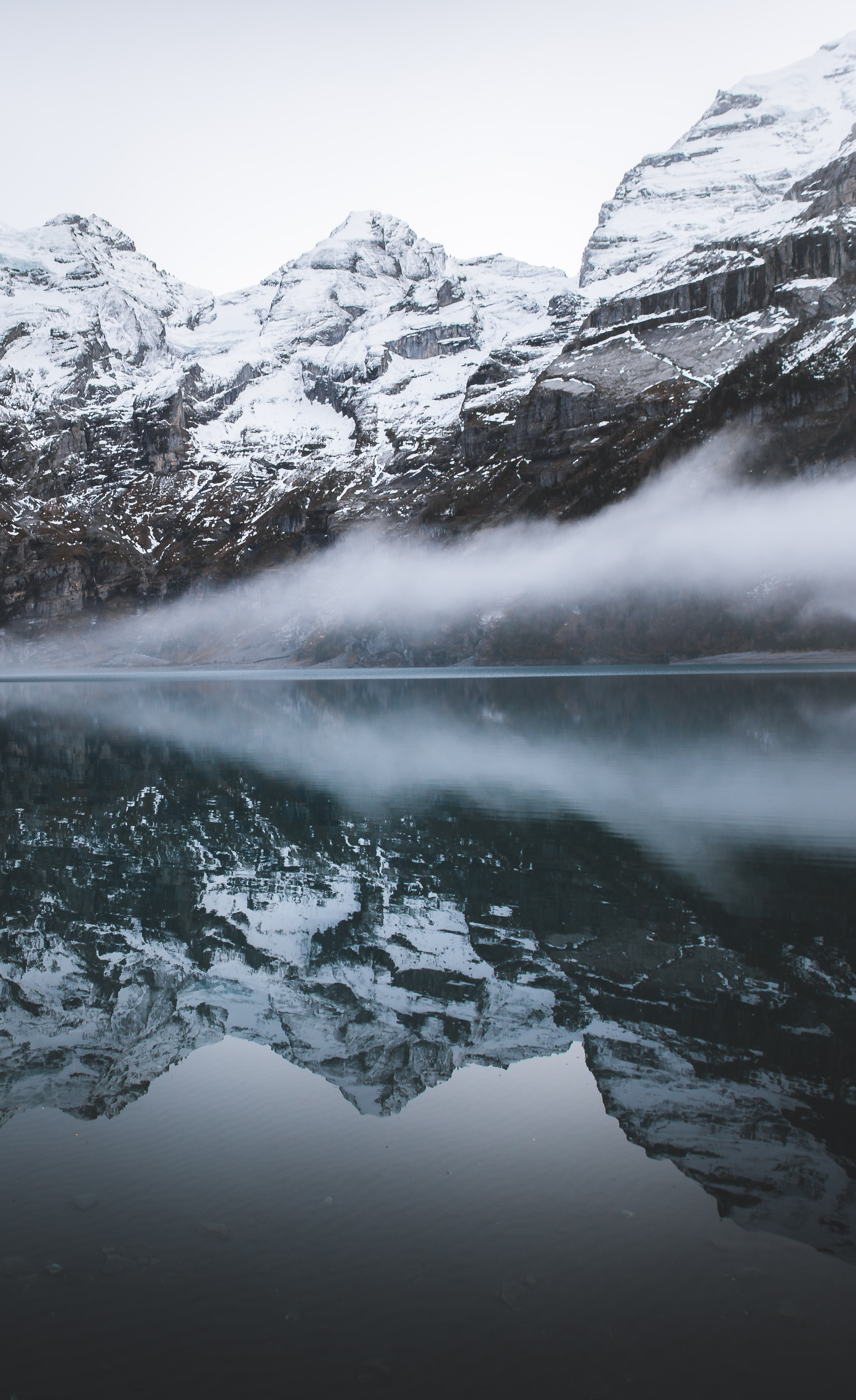 Reflections of snowy mountains reflect in calm foggy waters of Oeschinen Lake