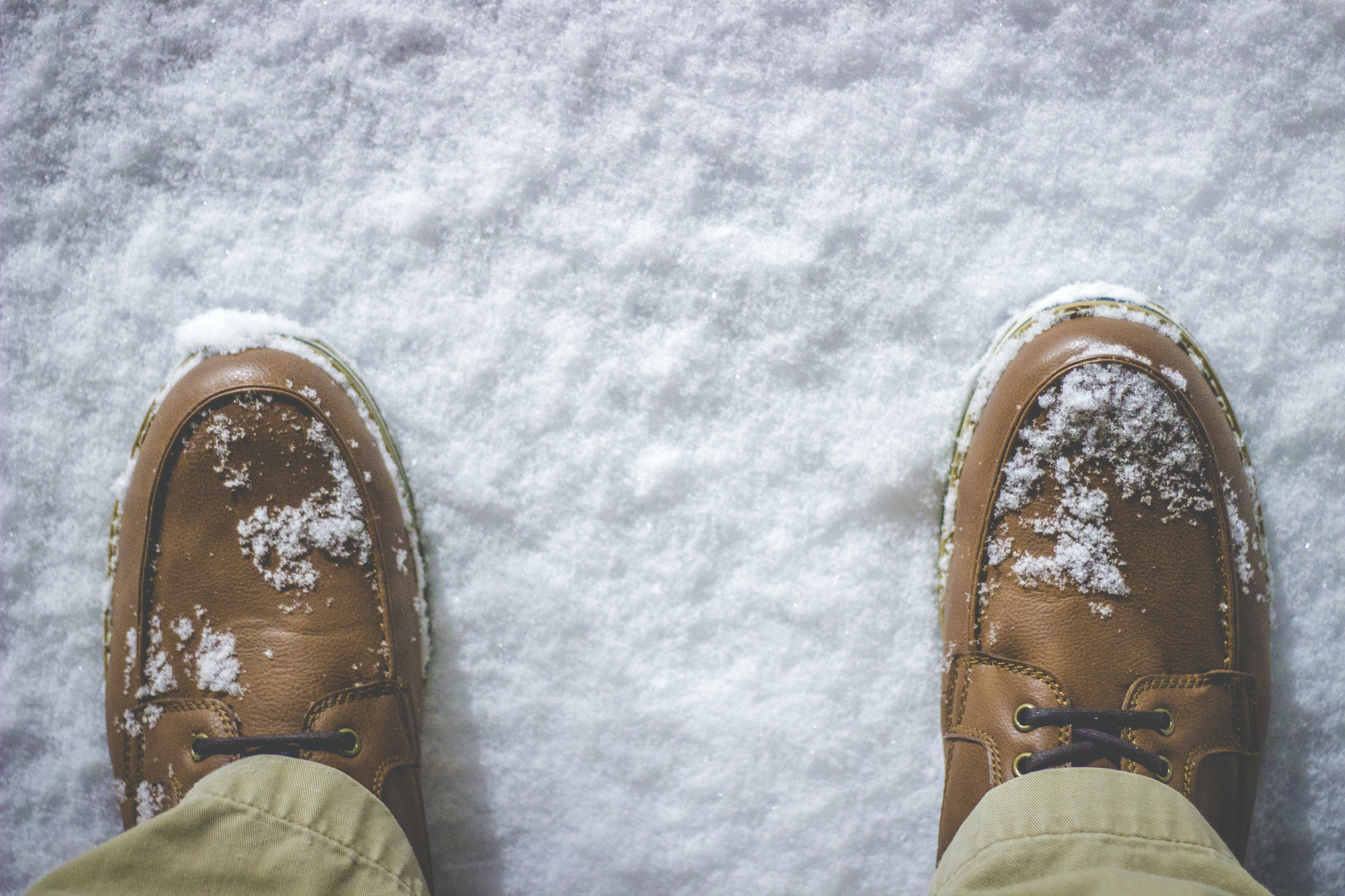Macro shot of a man's shoes with snow on them, taken in Battle Creek