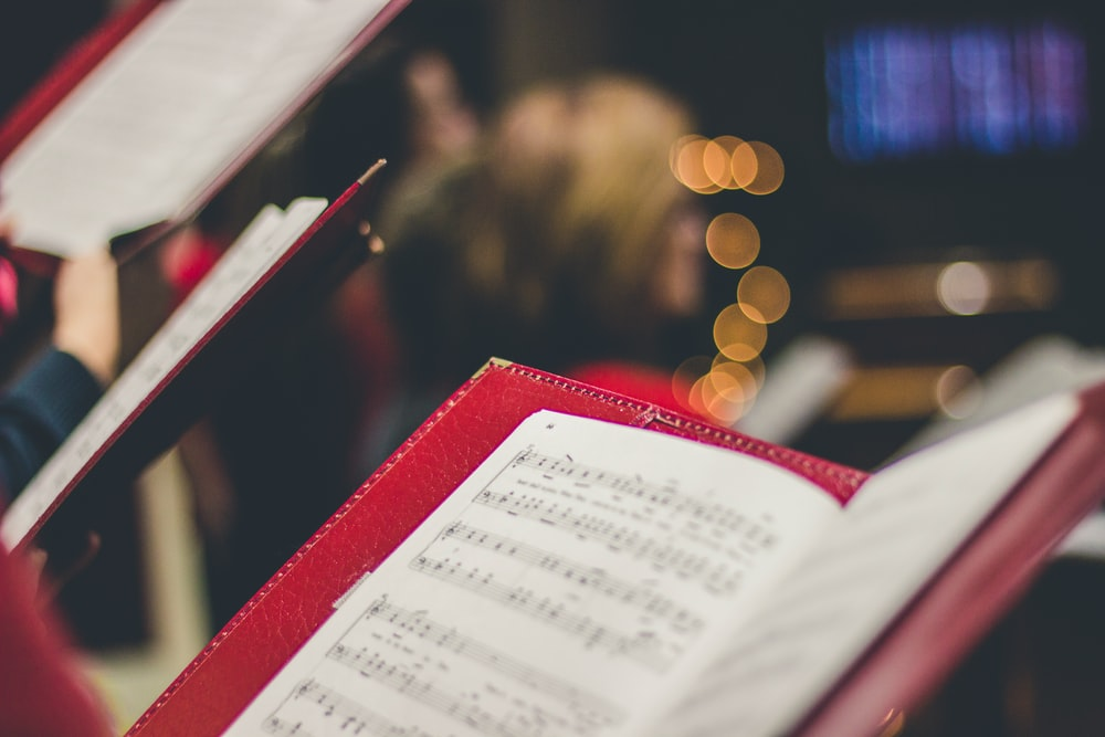 A close-up of a music score in a red leather case with bokeh effect in the background