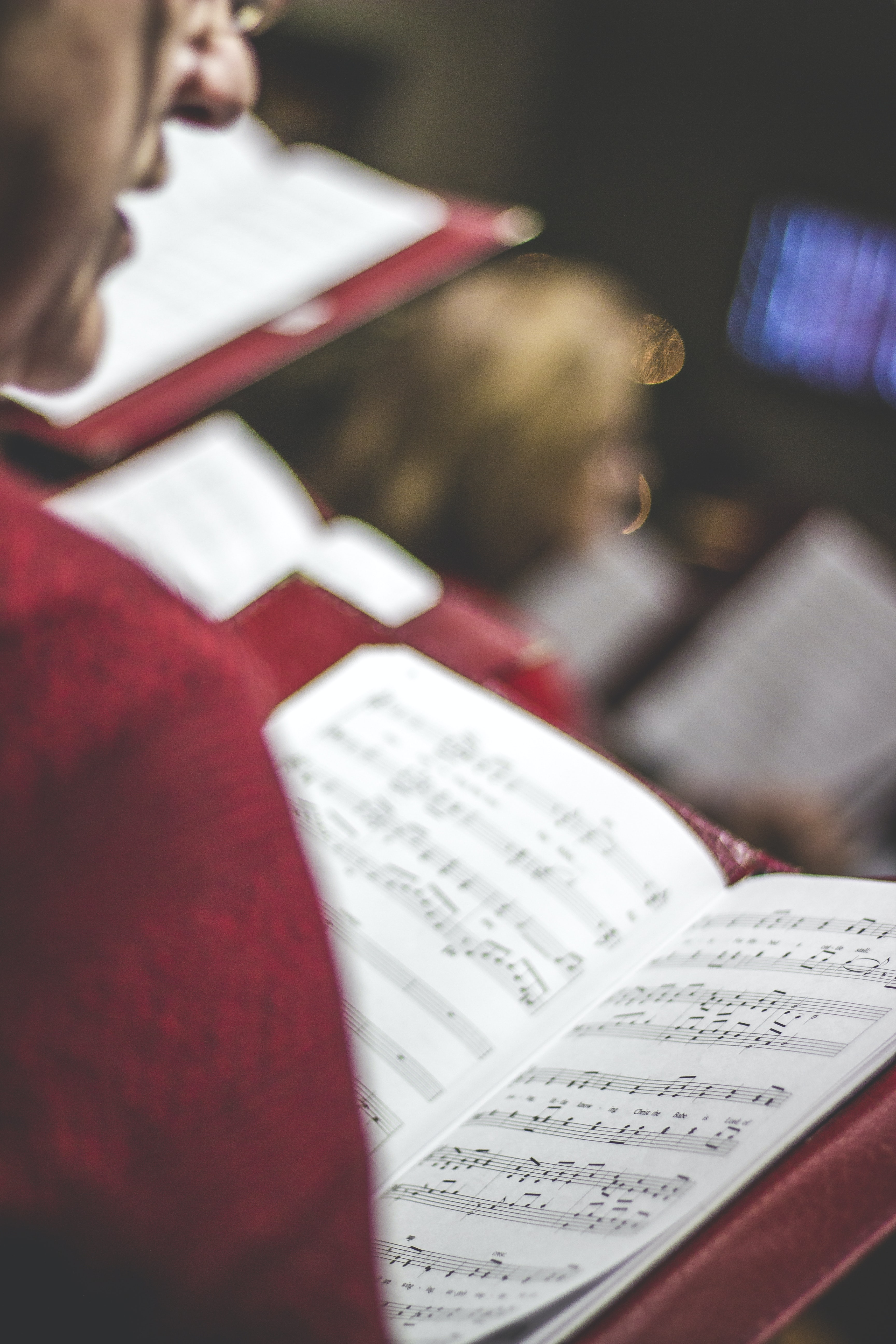 A member of a chorus singing while looking down a music score in a red leather case
