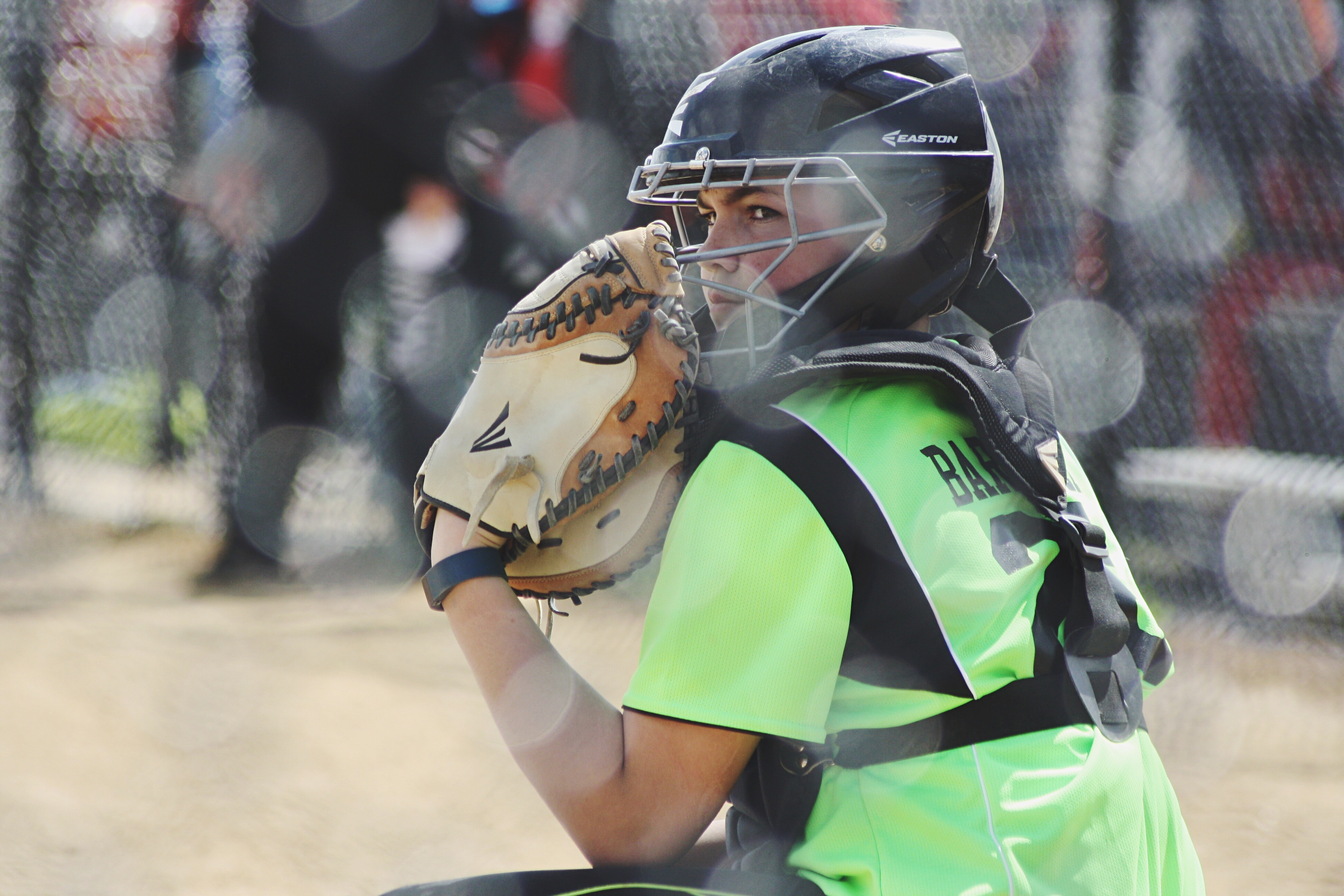 A female catcher staring in a baseball stadium while wearing a glove and mask