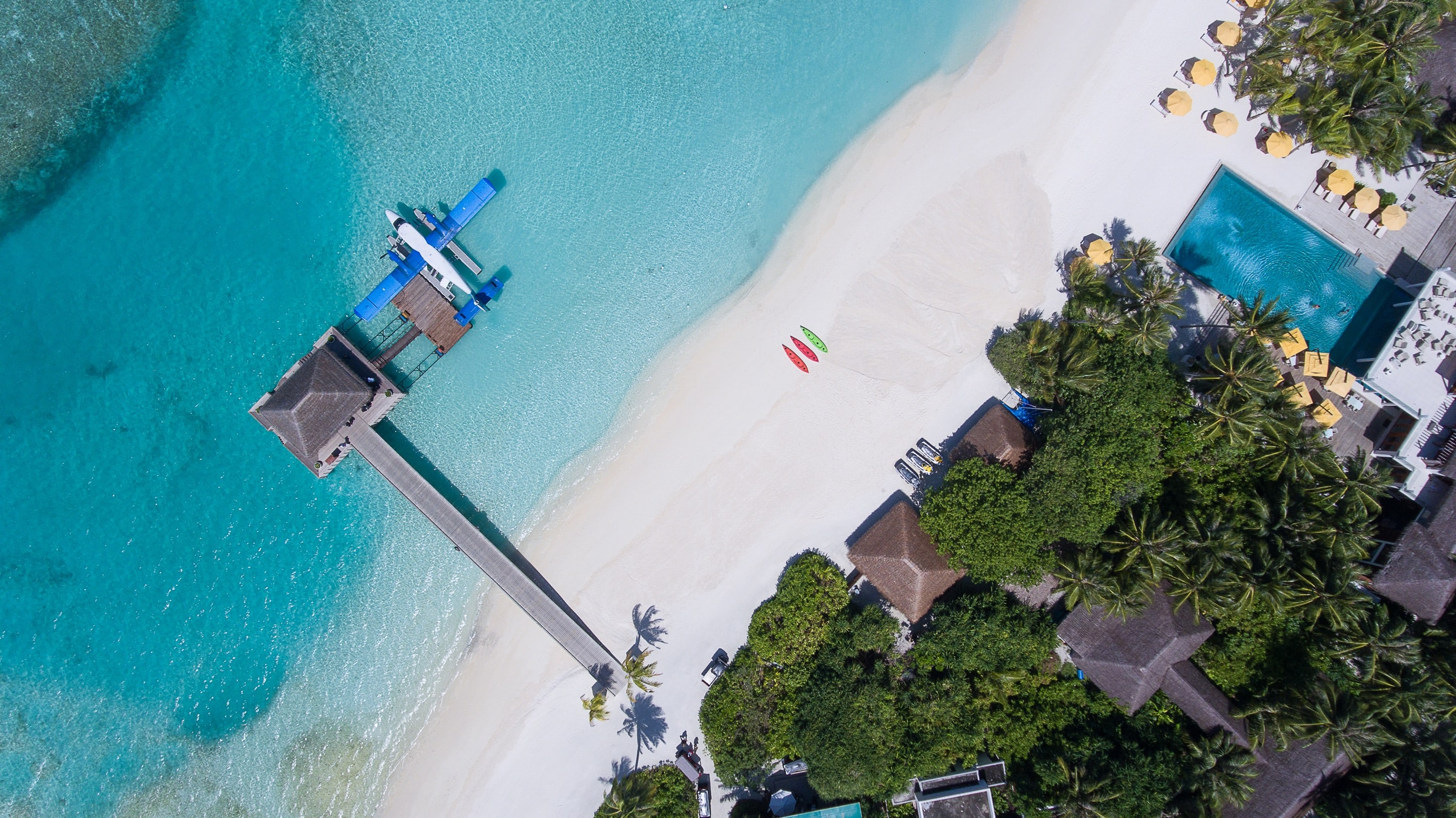 Drone aerial view of an airplane docked at the pier on the sand beach in Per Aquum Niyama