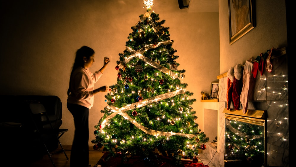 child standing in front of Christmas tree with string lights