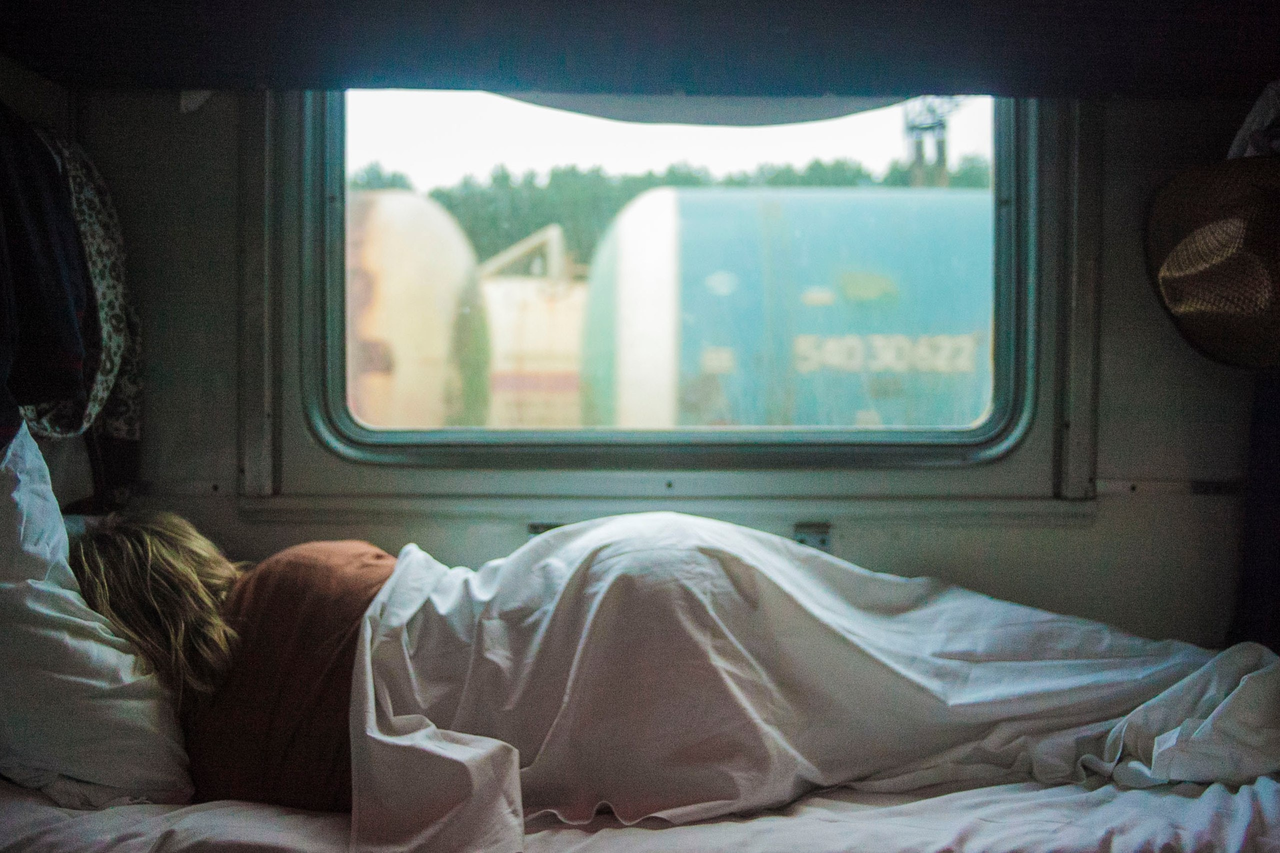 Blonde woman sleeping in pink sheet bed next to window in daytime Penza