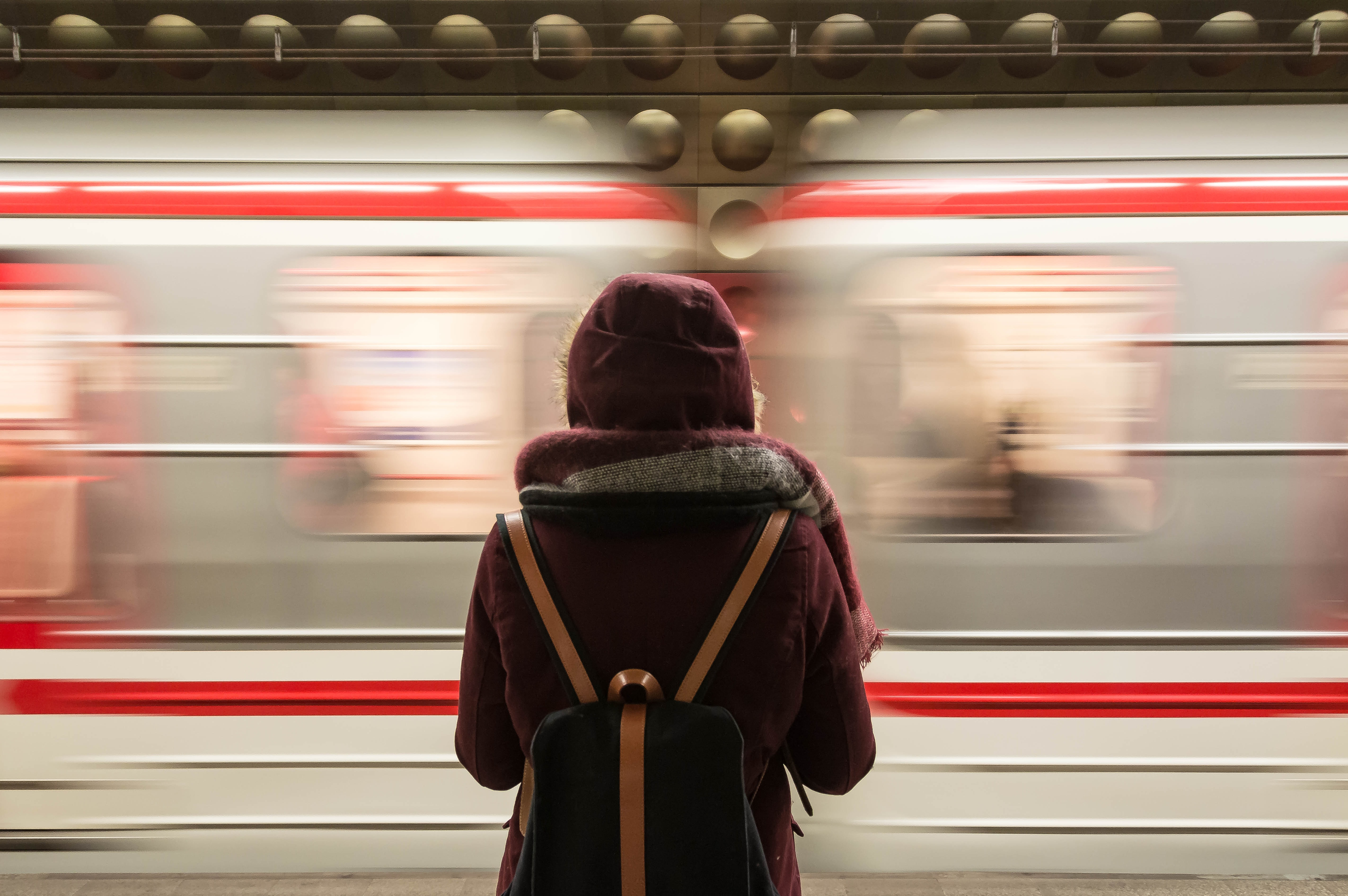 time-lapse photography of woman standing in front of train