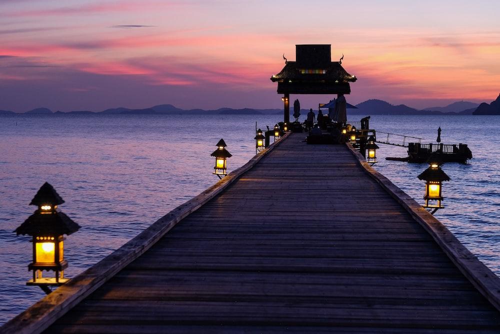Lamp lit sunset along Koh Yao Yai Pier facing towards the sea