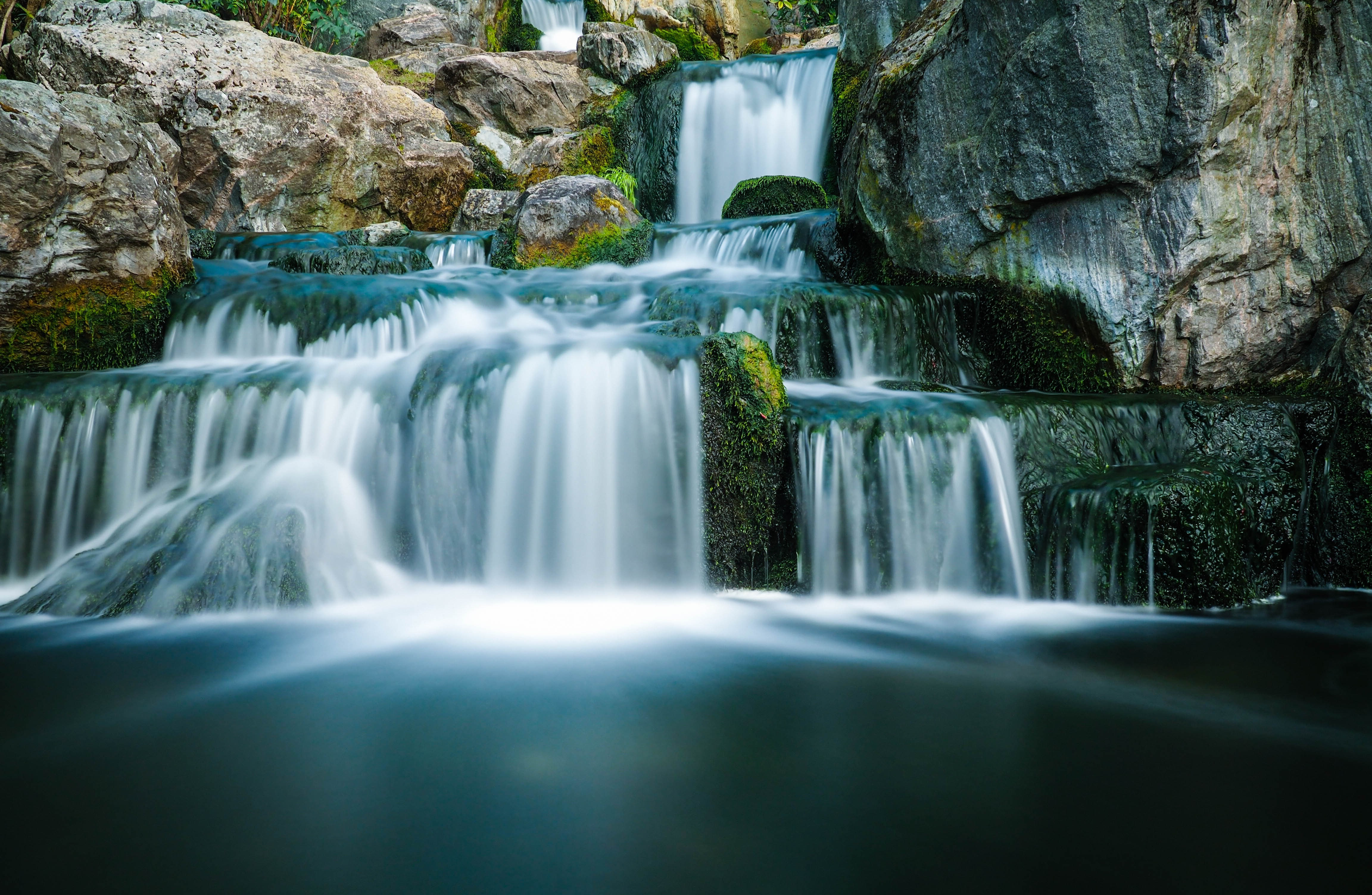 A staggered waterfall in motion flowing through a mossy rock mountain in Holland Park