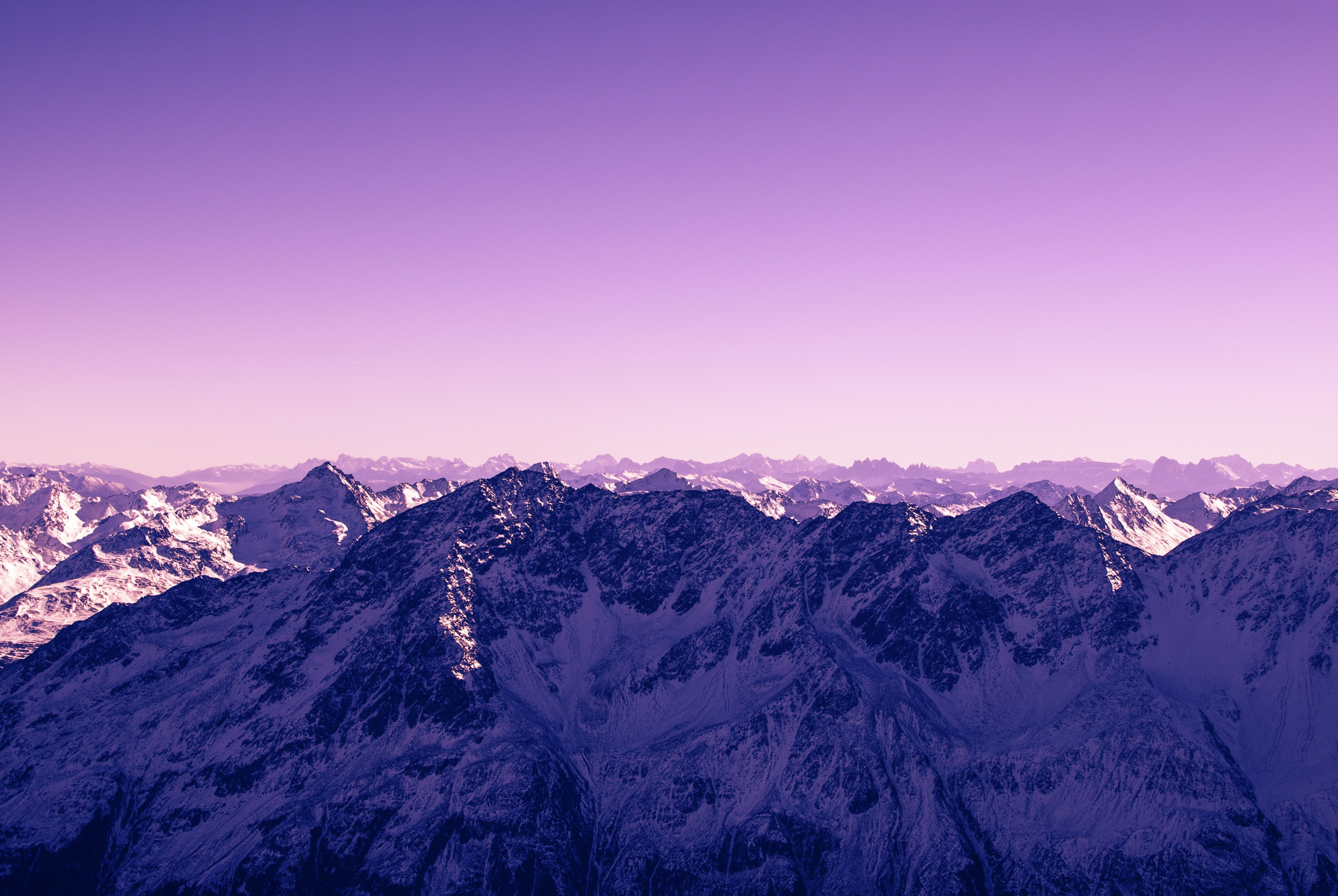 A pink-hued sky over tall snow-capped mountains in Austria