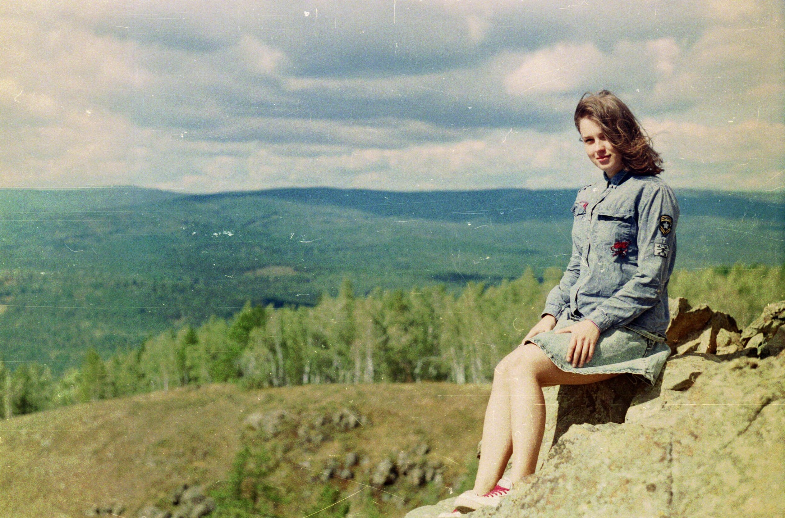 Retro film image of a happy woman sitting atop mountains