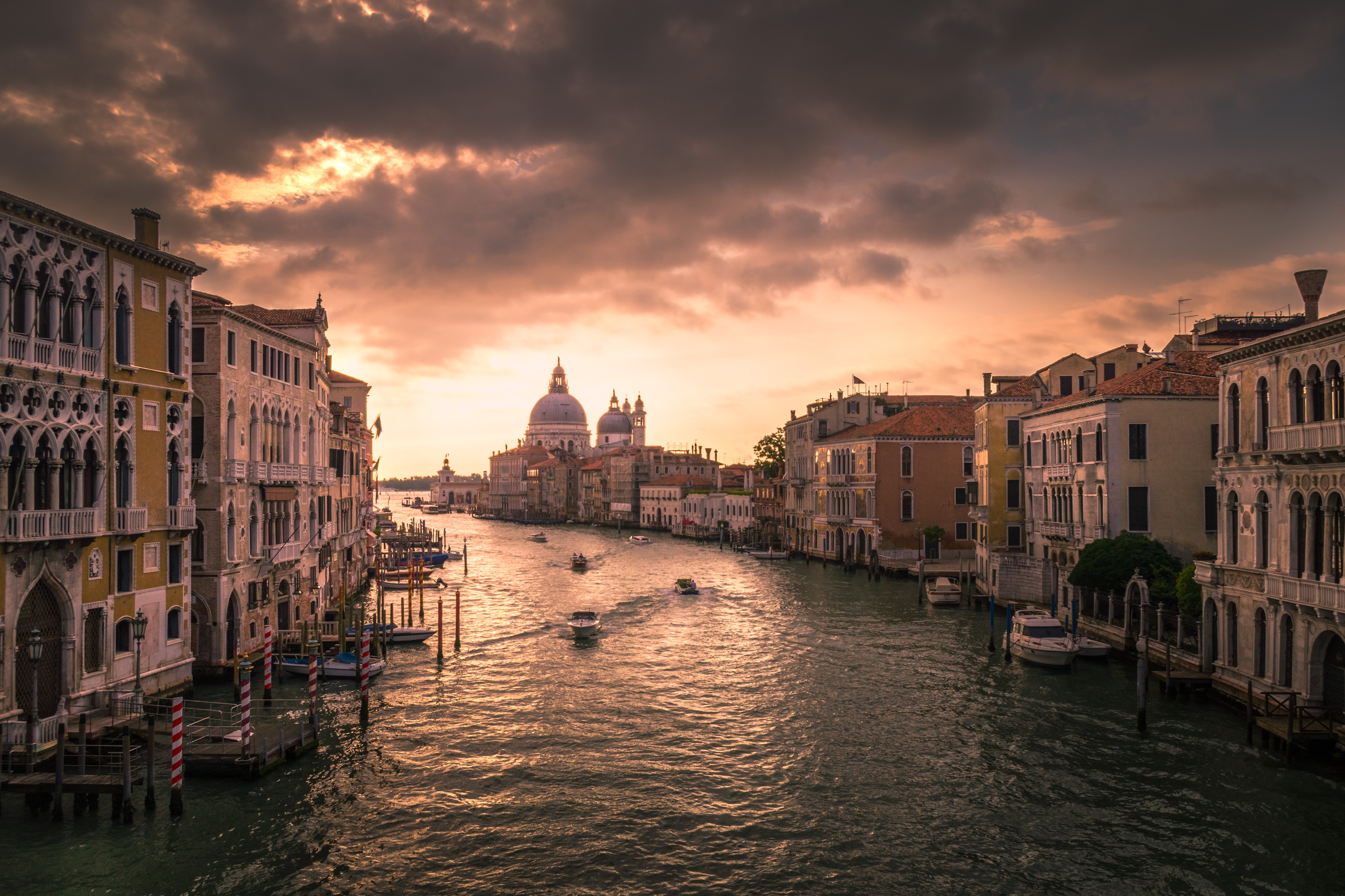 Two rows of buildings surrounded by water and sunset in Venice