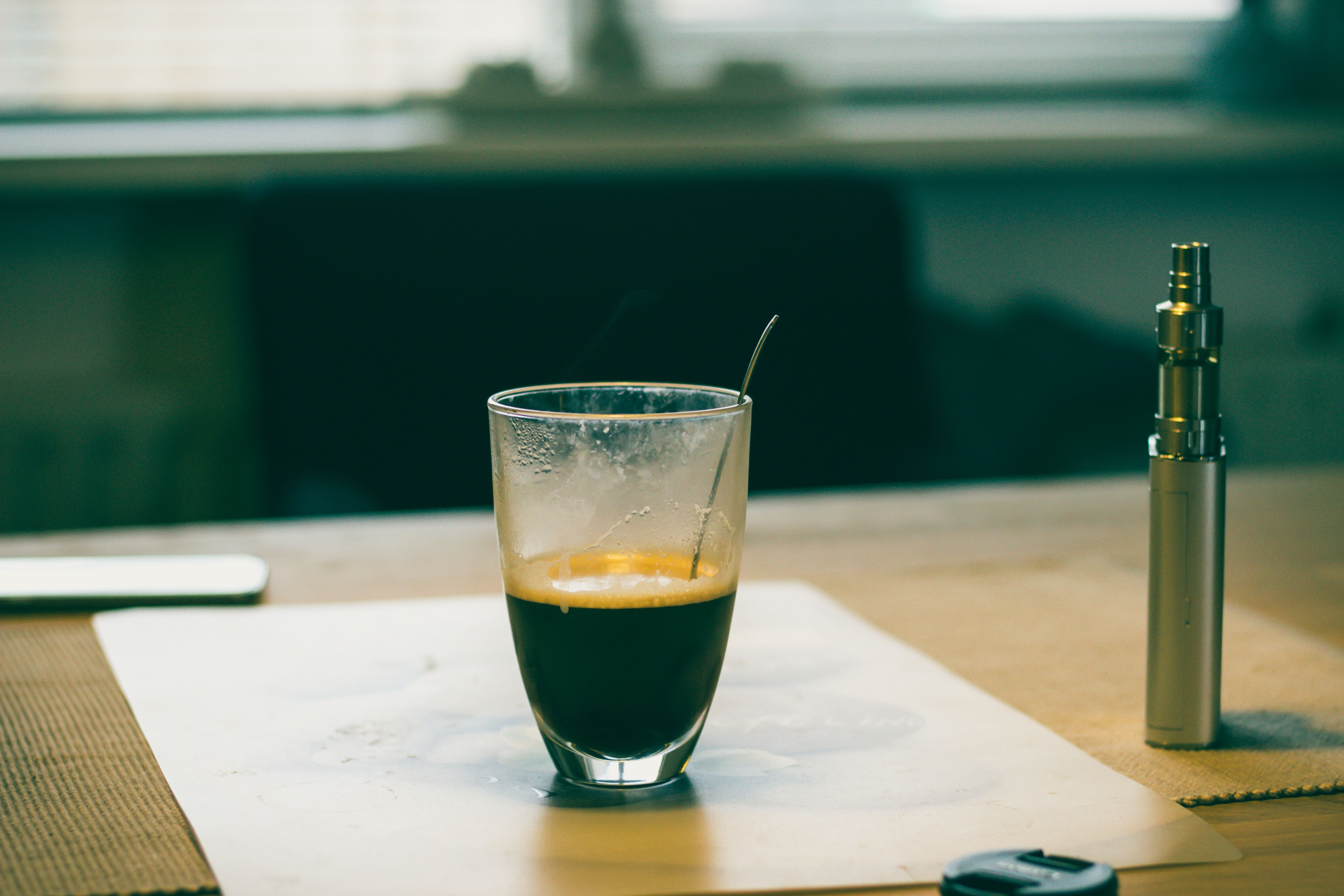 A glass cup of coffee placed on a paper on a table