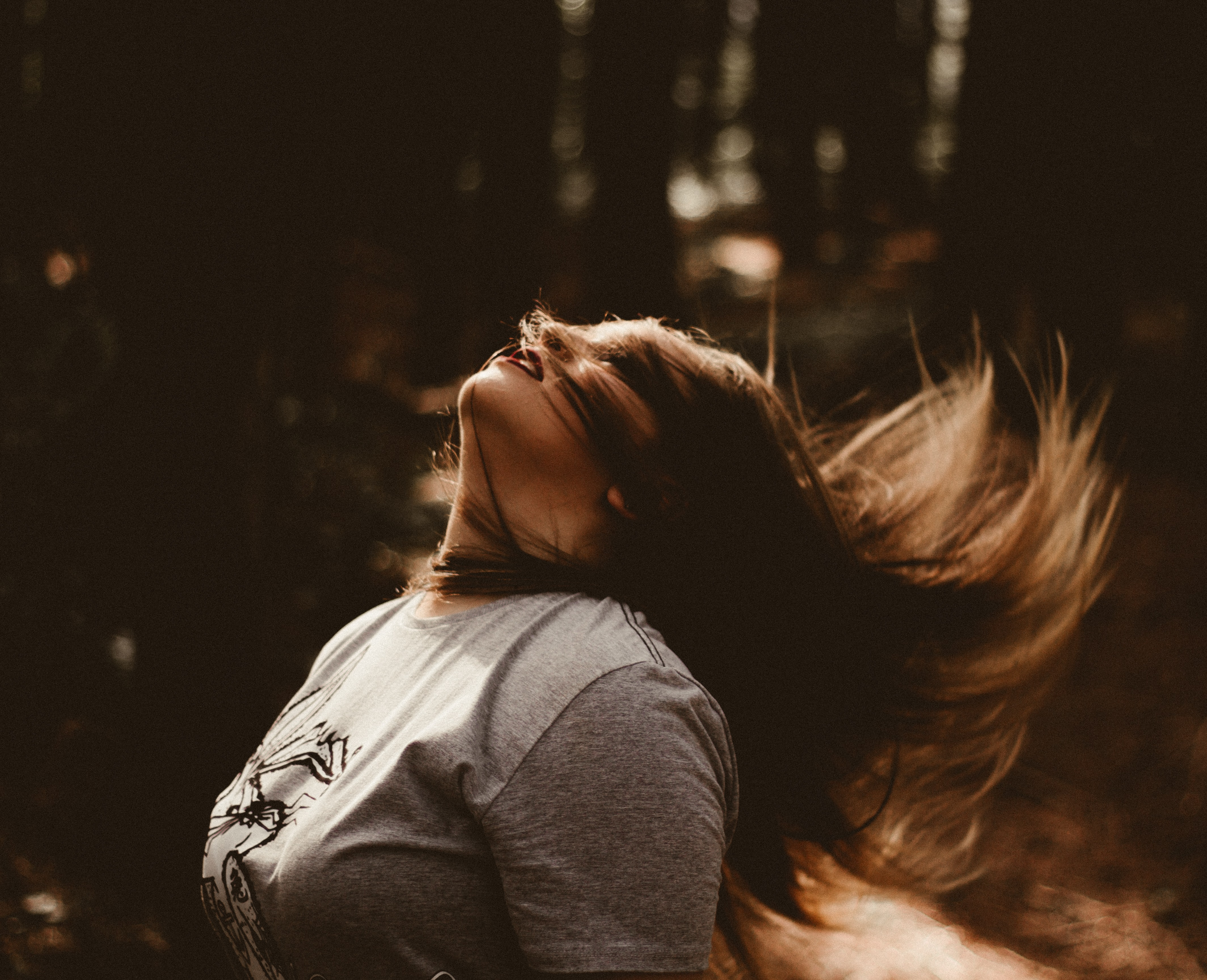 Woman flips hair back in the woods