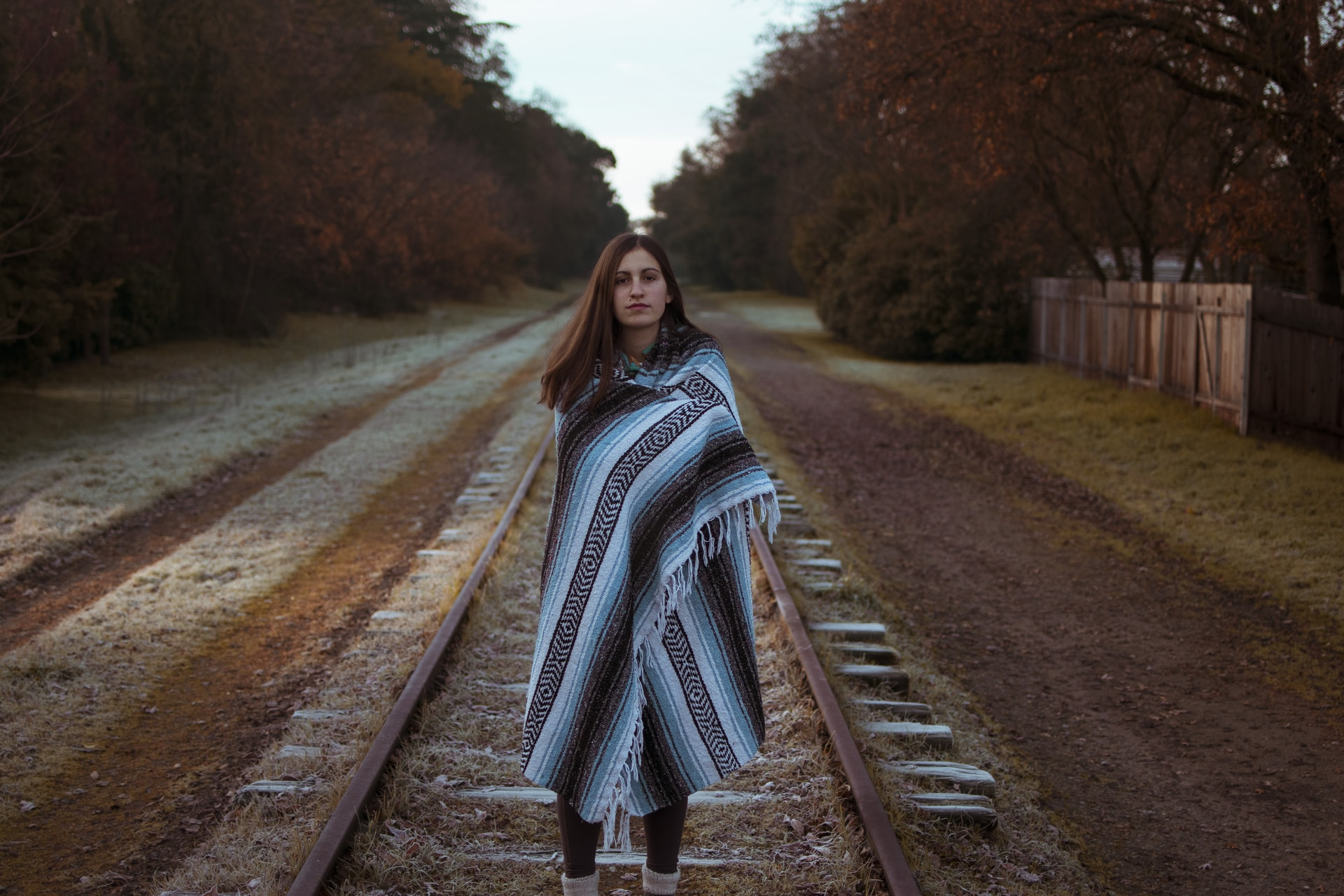 woman with blue and black striped scarf standing on brown train railway during daytime