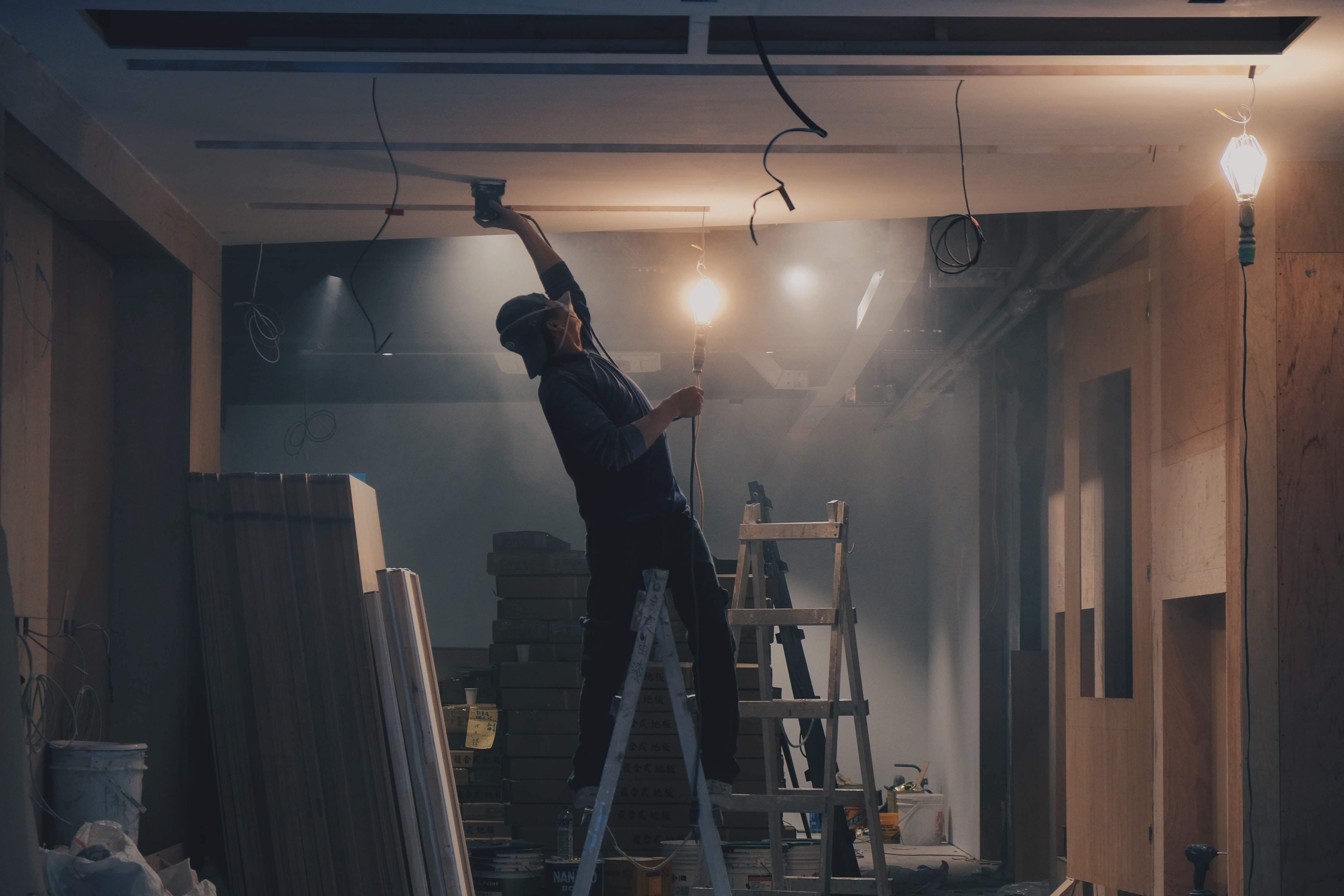 A man on a ladder renovating a room
