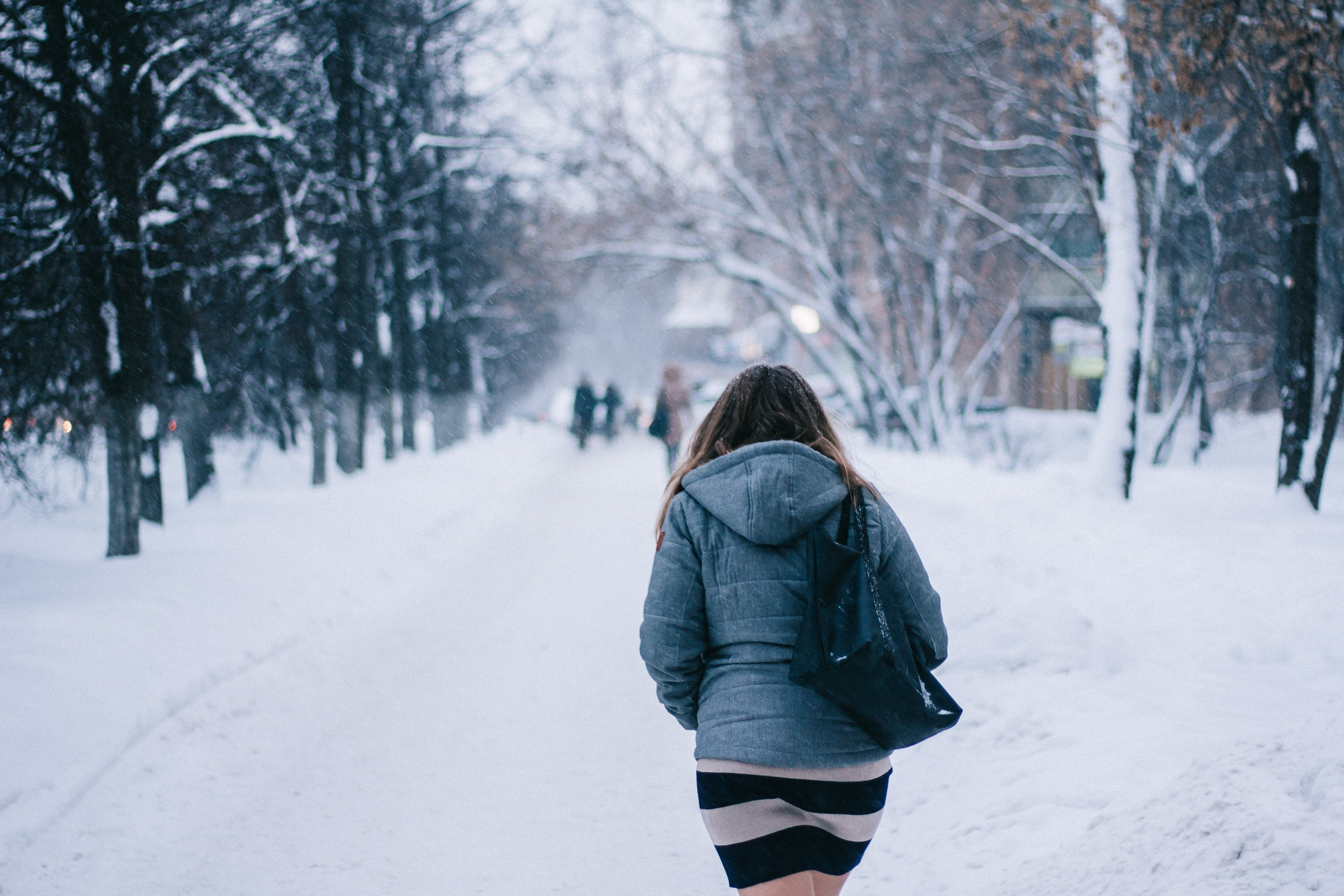 A woman wearing a skirt and jacket, walking through the snow on a treed road