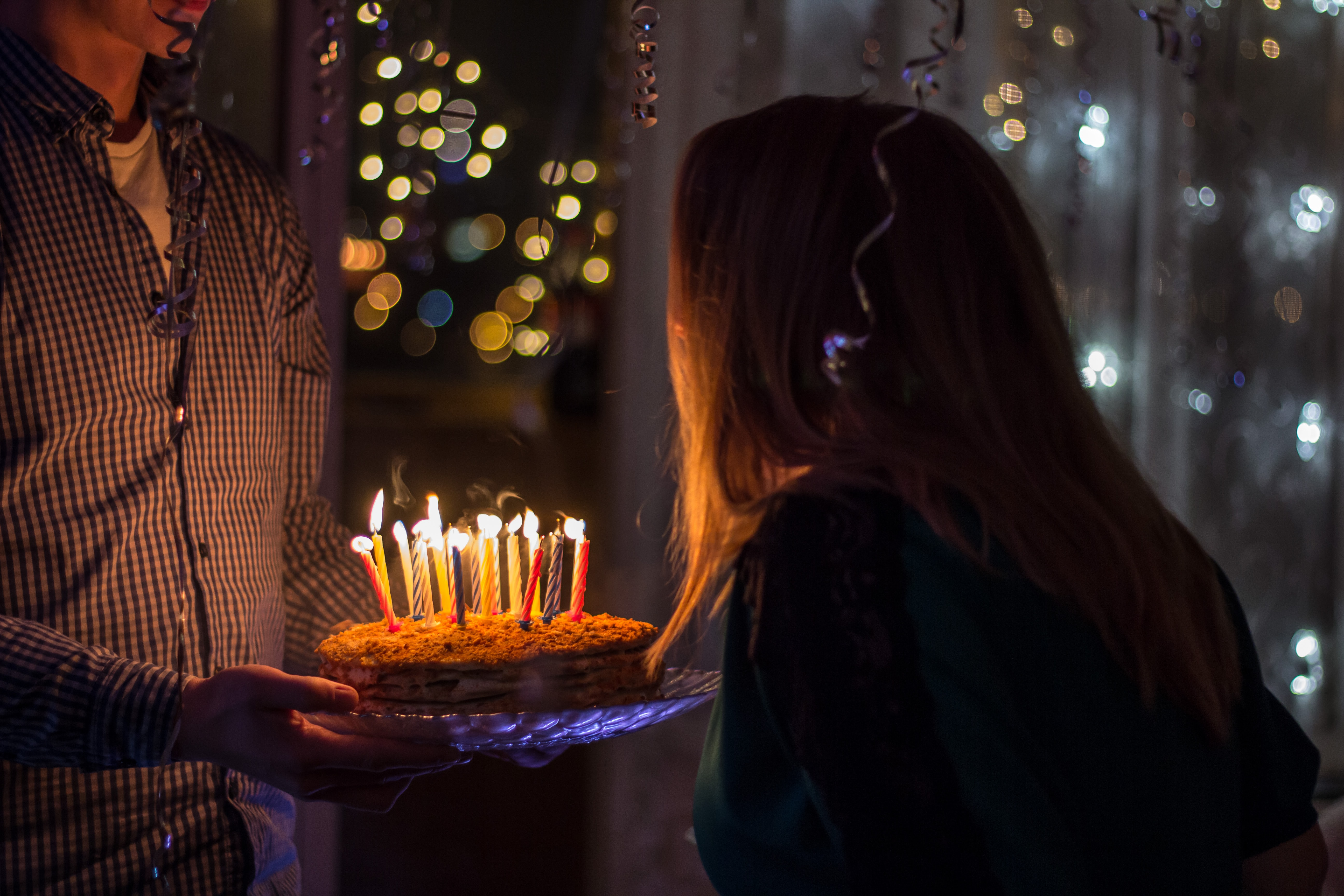A man bringing a birthday cake with candles to a woman in a room filled with balloons