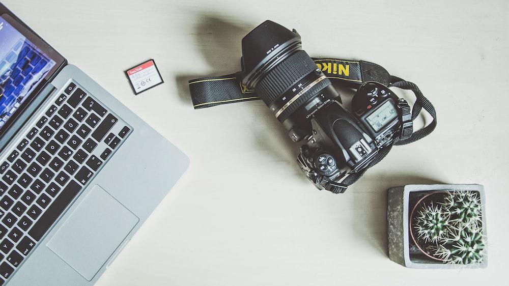 black nikon dslr camera beside silver macbook