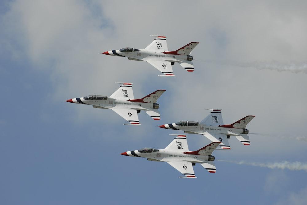 four white jet planes flying during daytime