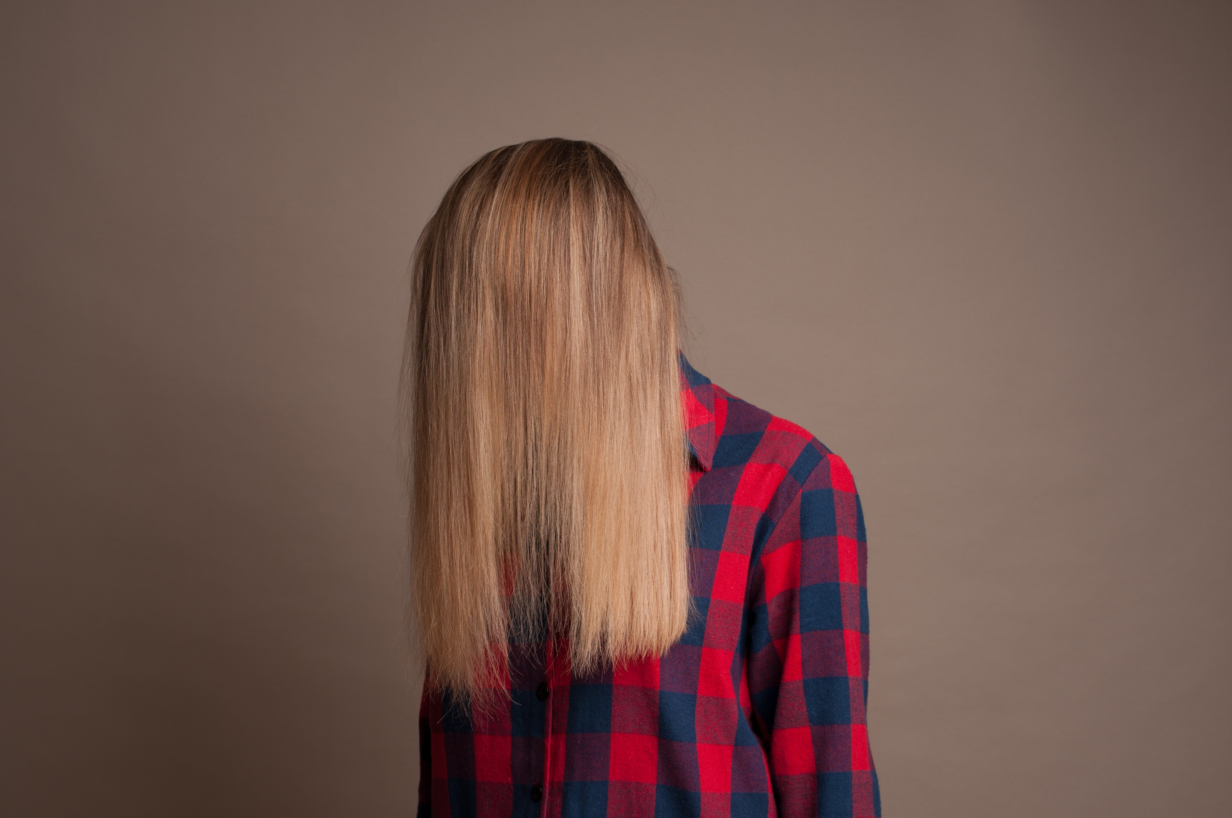 Person with straight blonde hair coverign their face
