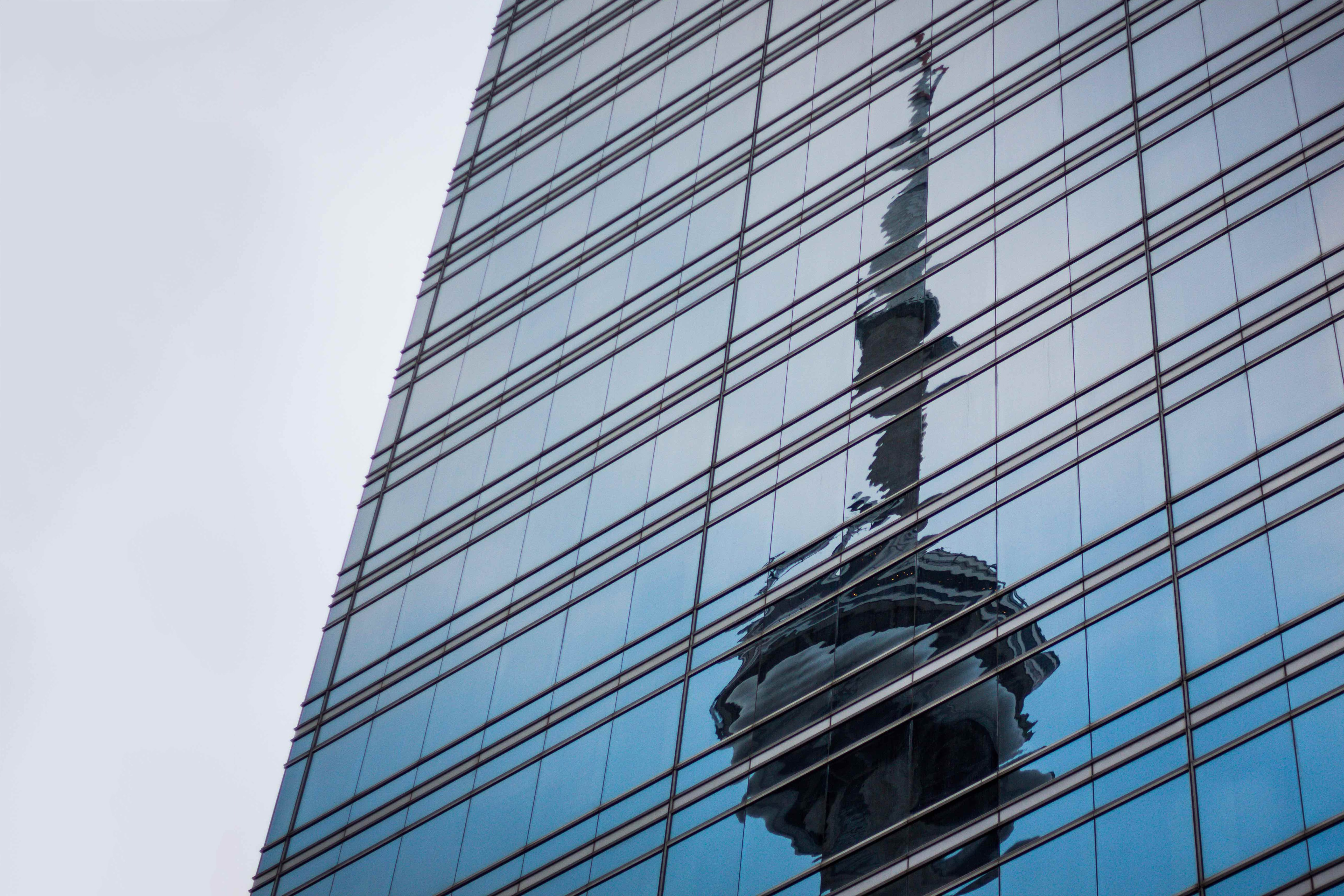 Corporate skyscraper window during daytime with reflection of CN Tower, Front West Street