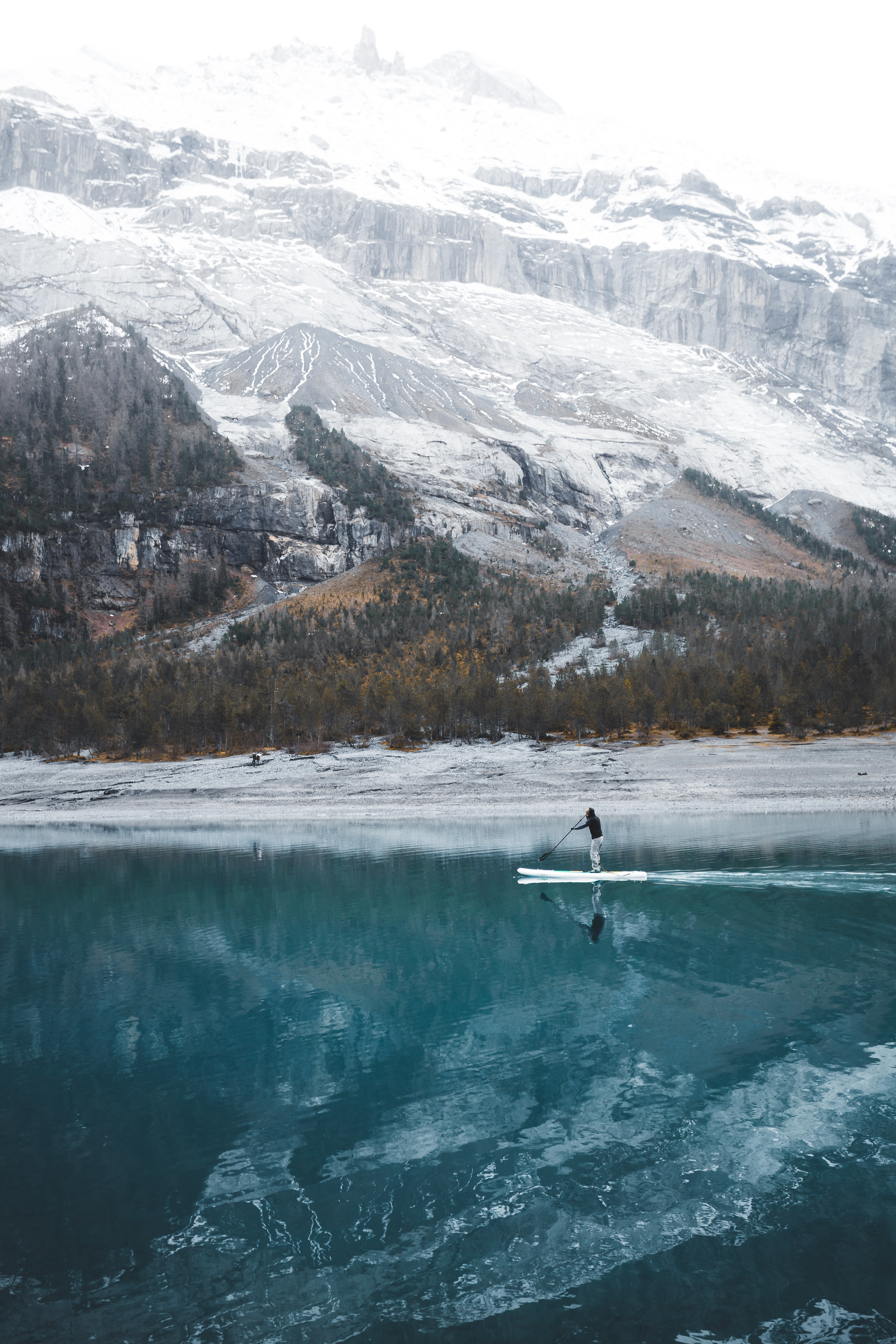 A man on a paddle board on an azure lake in the mountains