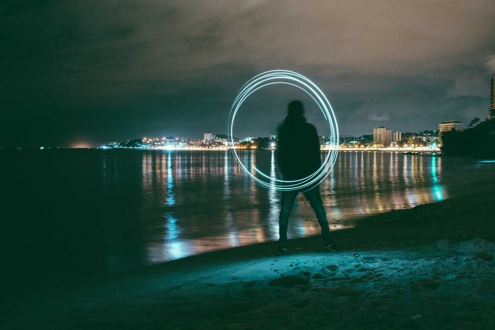 time-lapse photography of man playing with steel wool near seashore