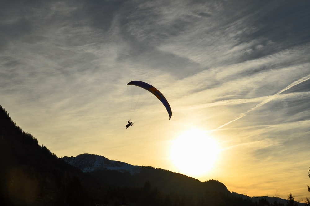 silhouette of person parachuting during sunrise