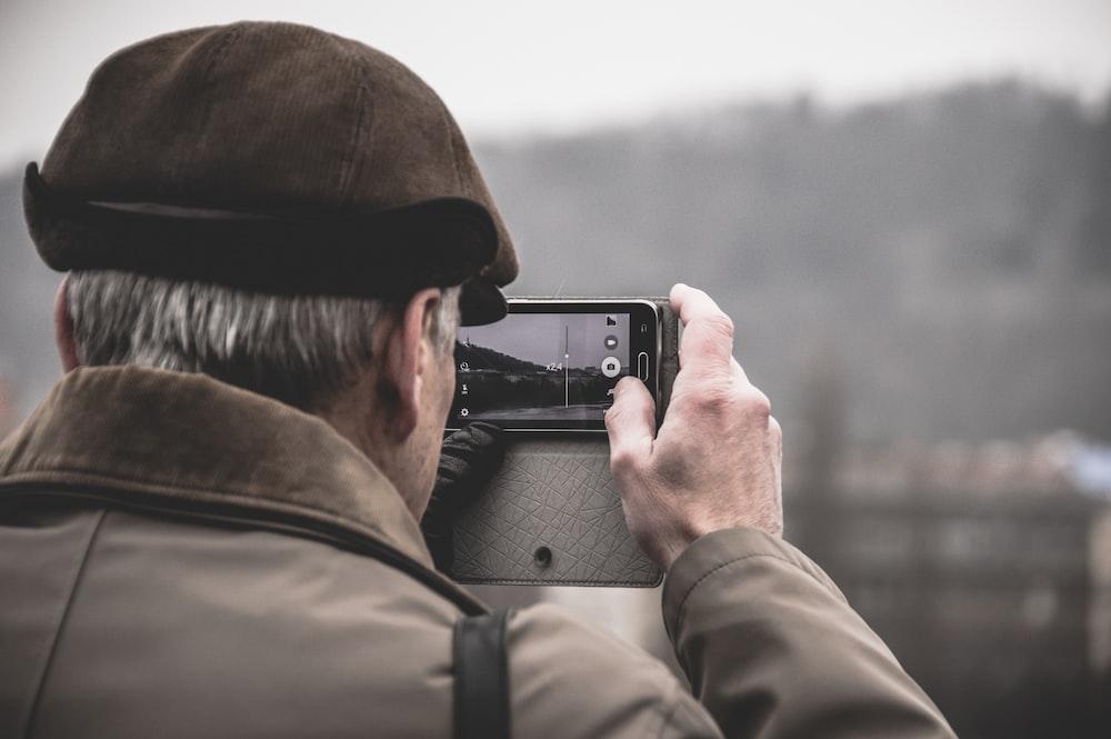 photo of man taking photo using camera
