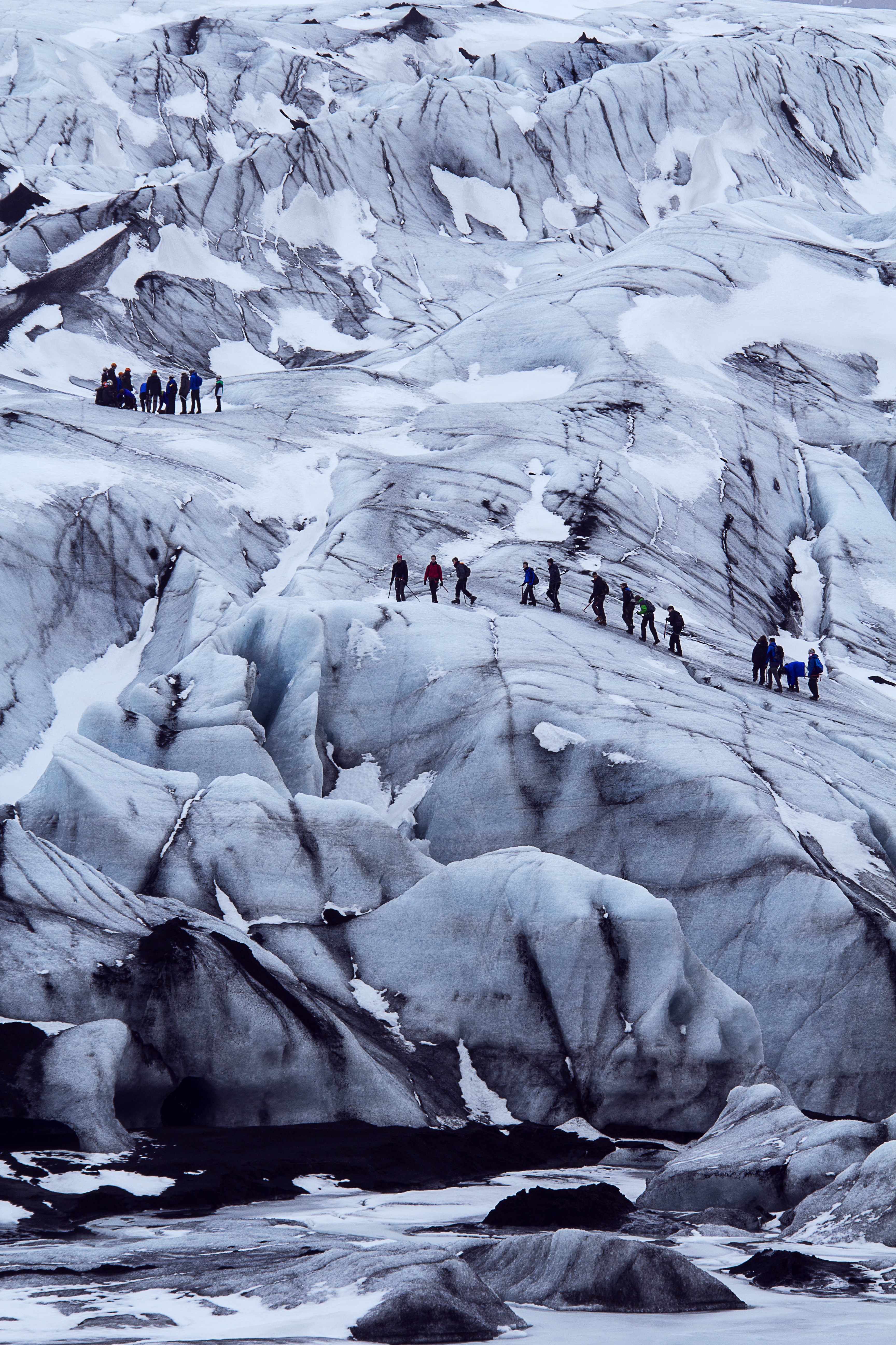A far back view of people hiking up the glaciers at Langjokull in Iceland
