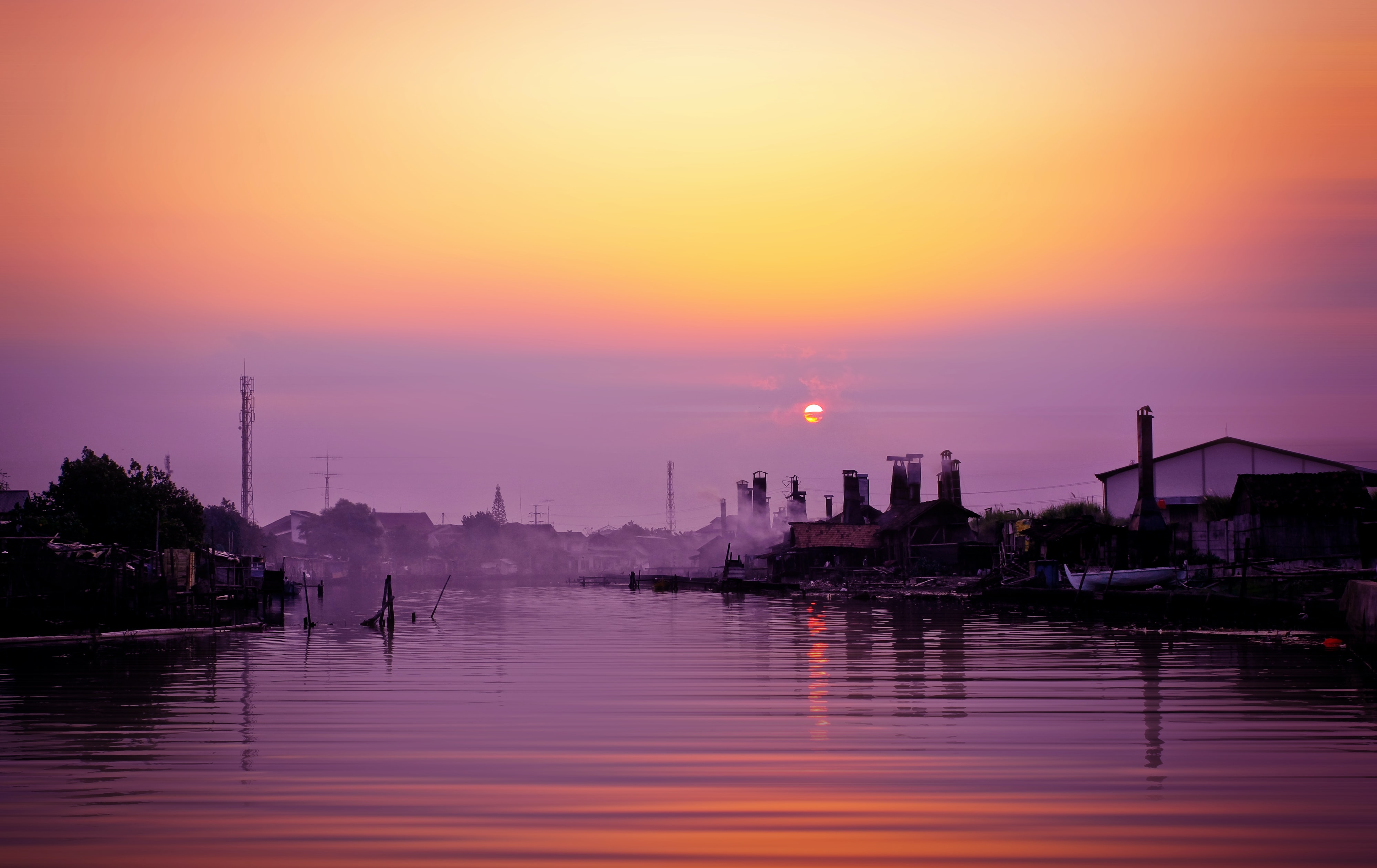 Buildings and boats on the rippling river, with a purple and orange sunset sky overhead, Semarang City