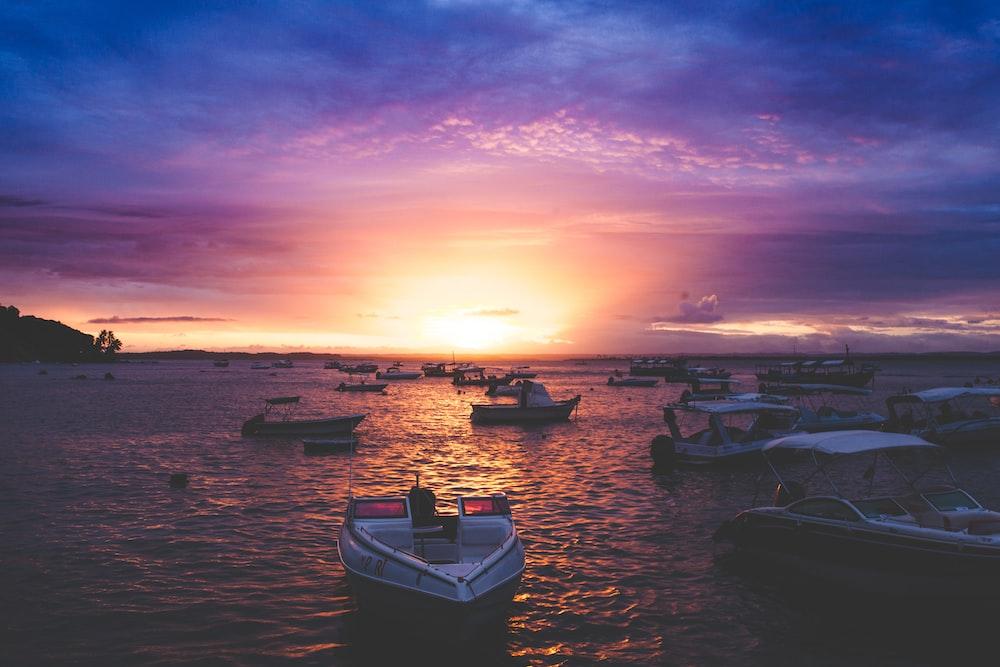 watercrafts in ocean during golden hour