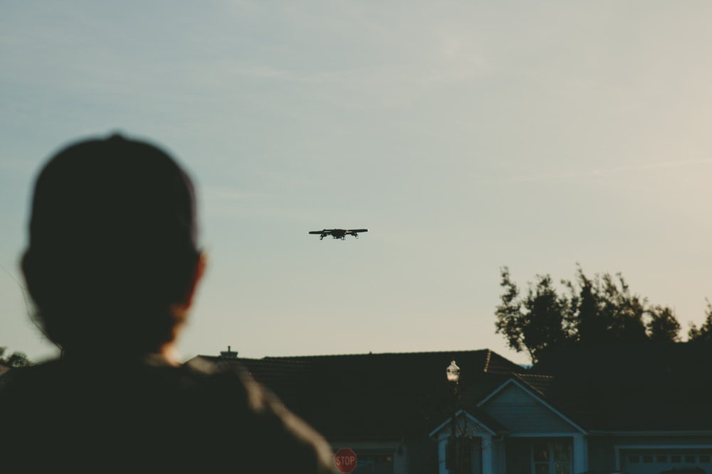man standing while watching plane on sky during daytime