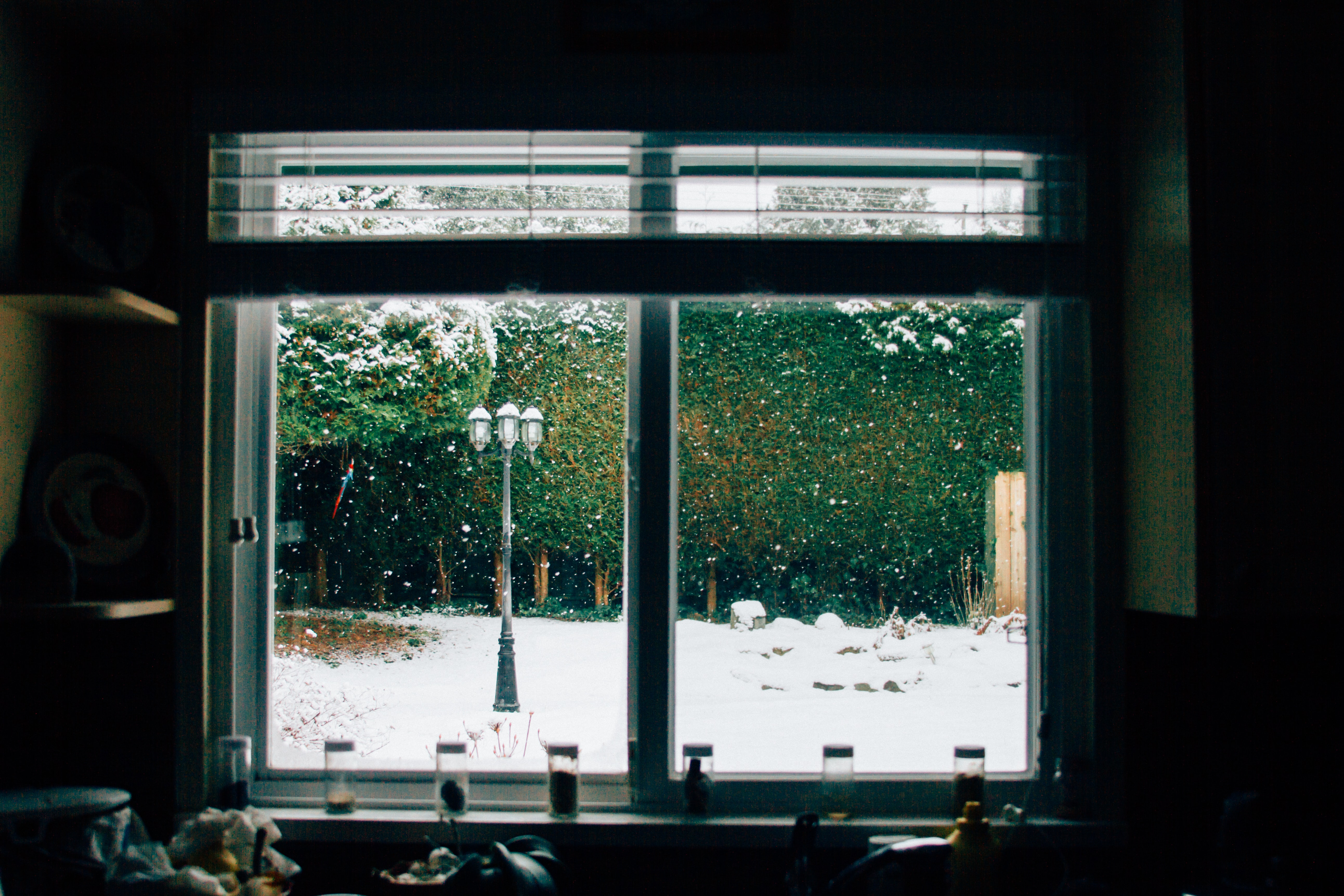 A cozy window looks out to snow falling on a lamppost
