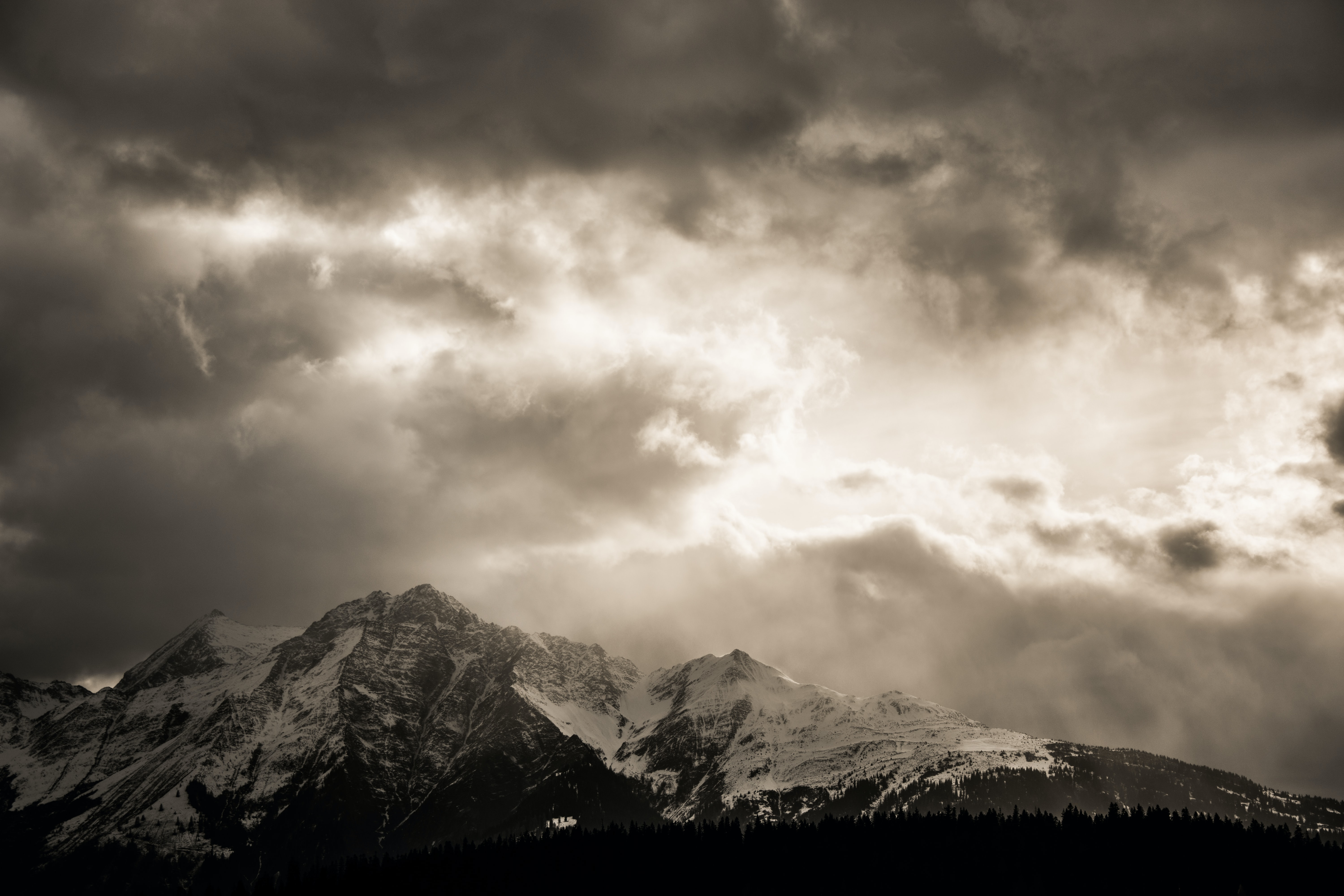 A desaturated shot of an overcast sky over a snowy mountain range in Flims