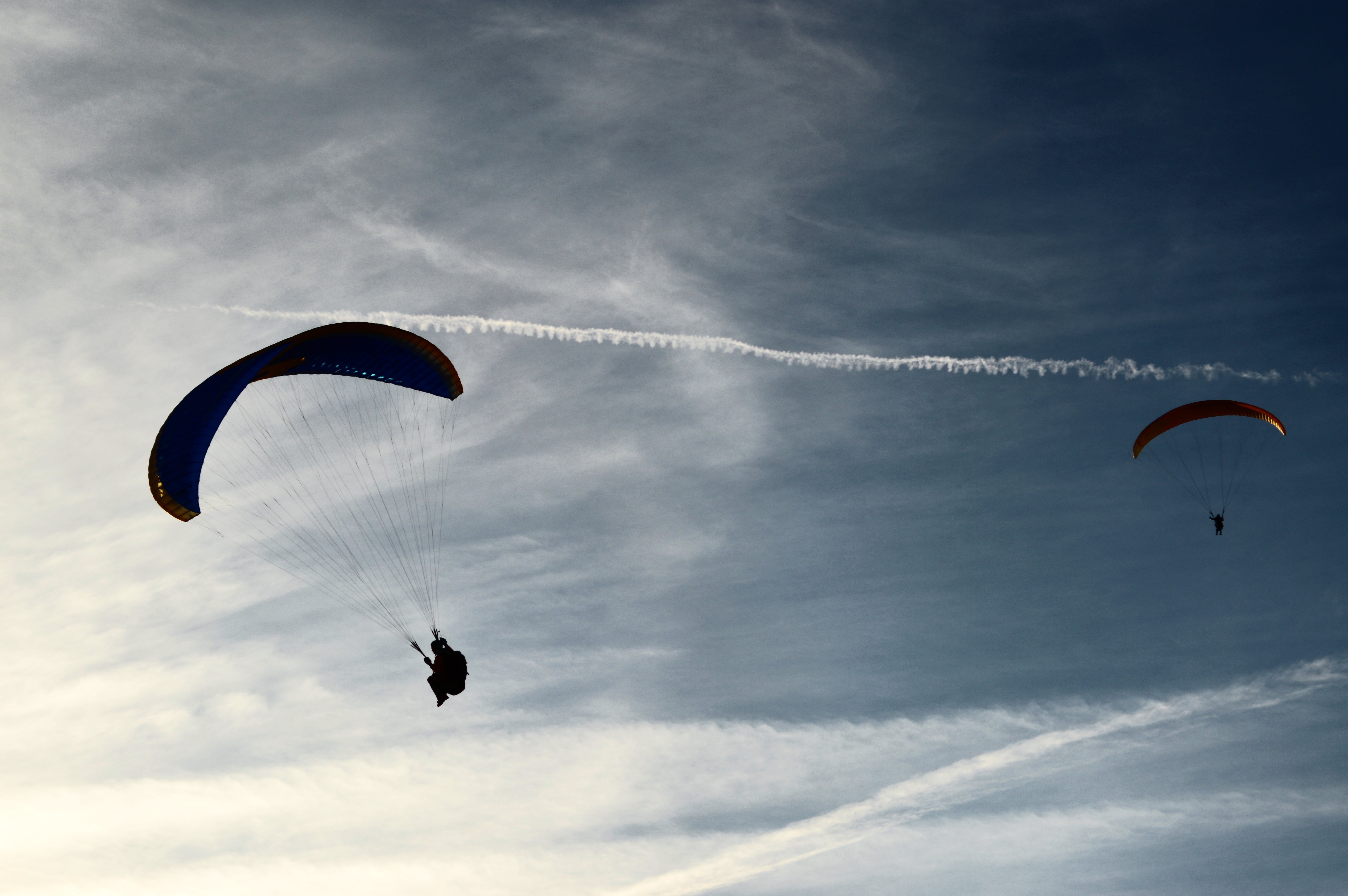 two people riding parachute on clouds during daytime