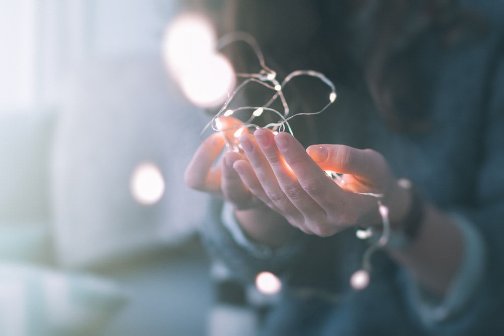 shallow focus photograph of person holding string lights