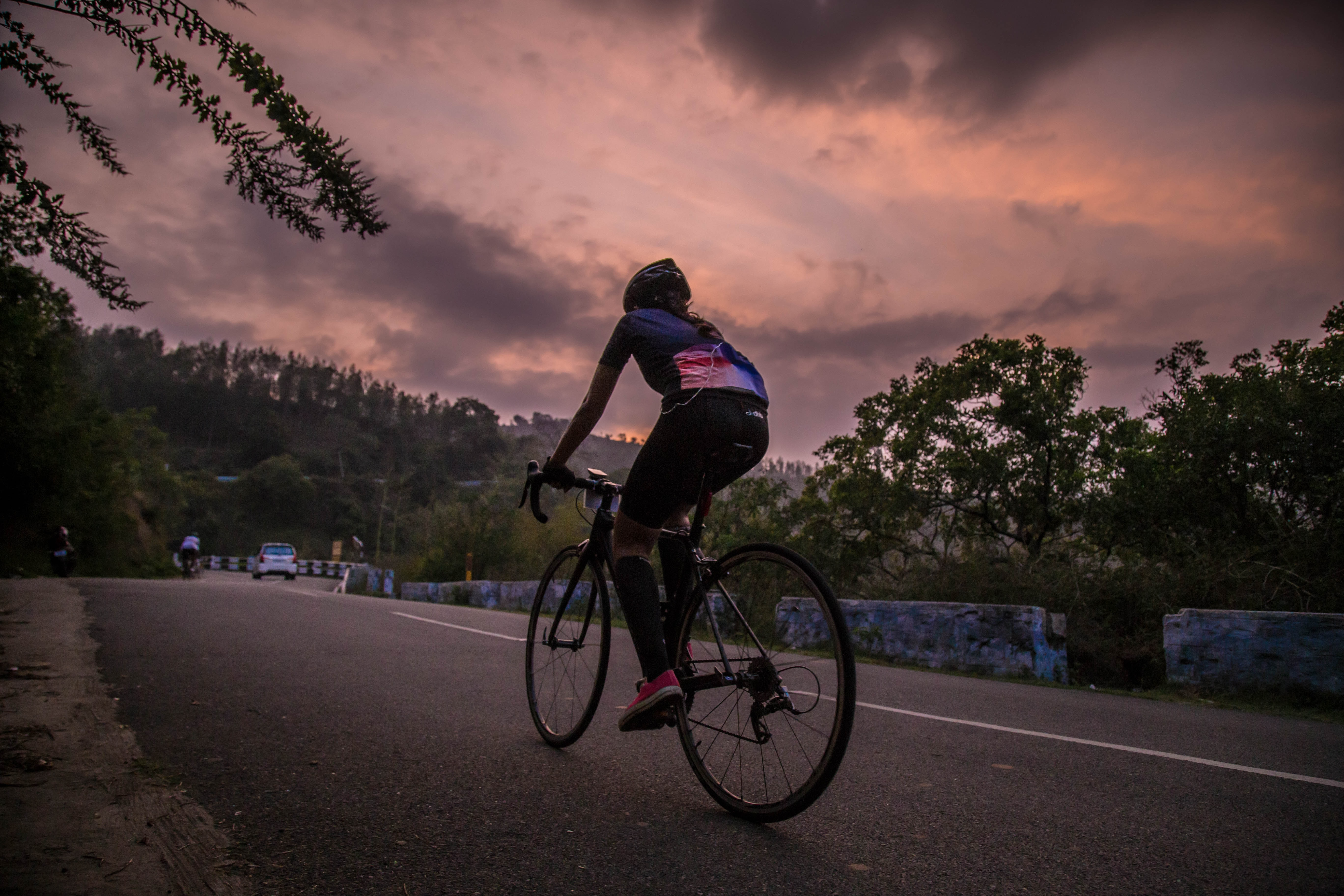 Male bicycling along a treed road in Ooty