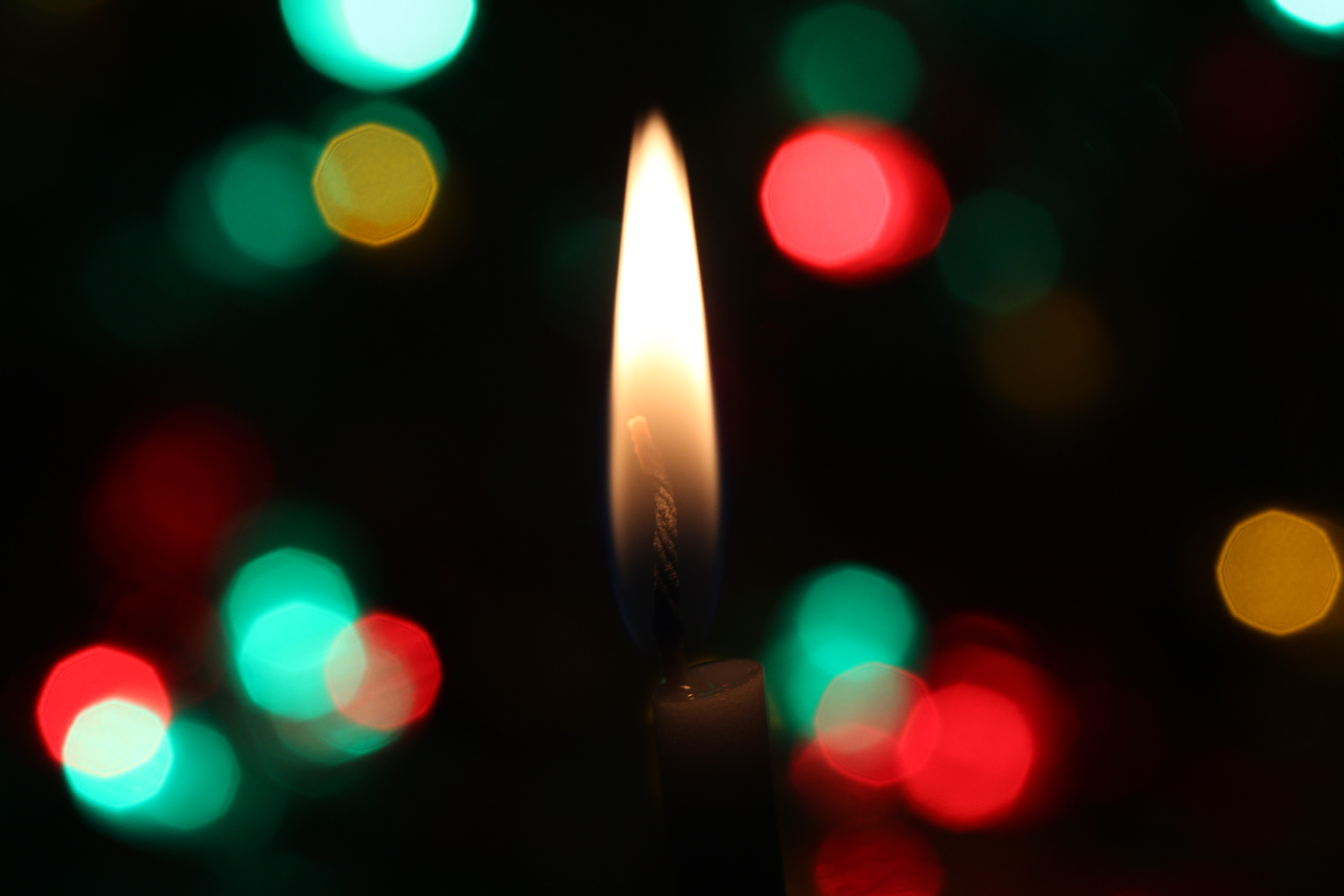 A candle flame burns between a bokeh of festive Christmas lights