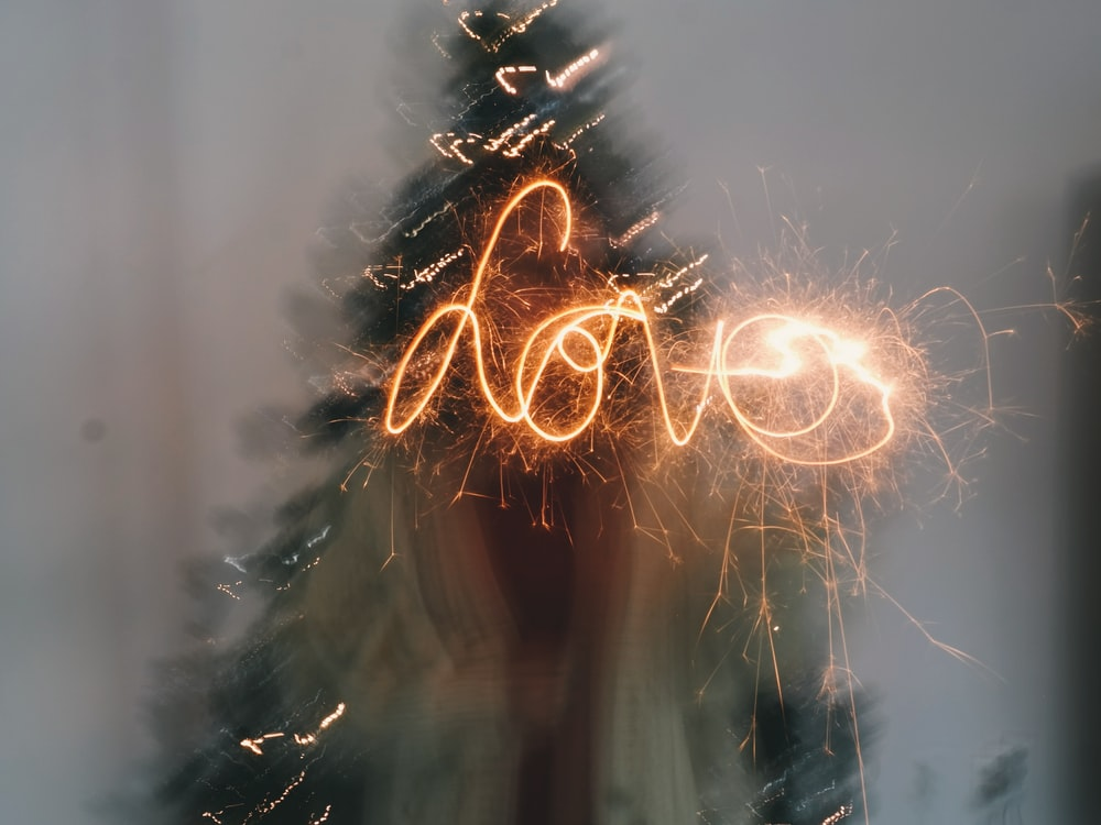 Person with a sparkler spells out the word love