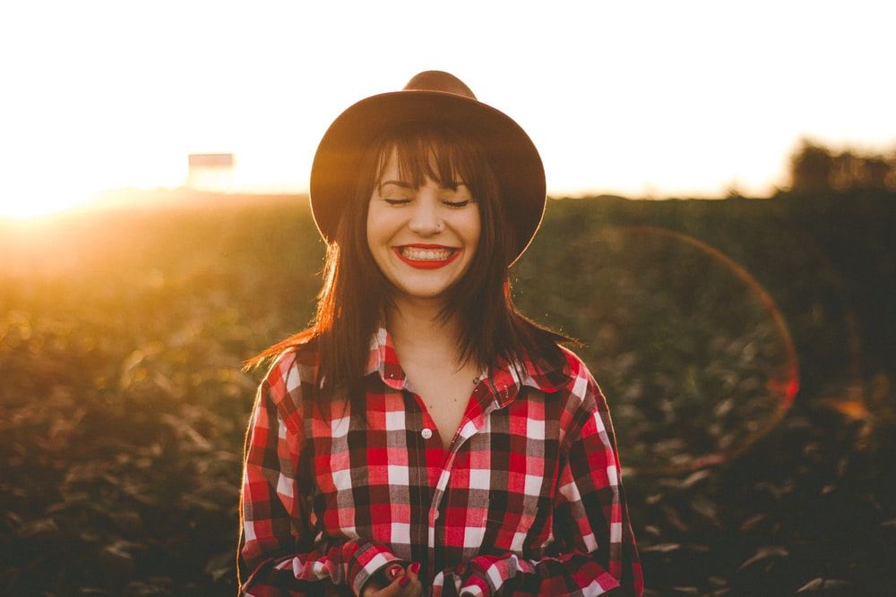 golden hour photography of woman in red and white checkered dress shirt