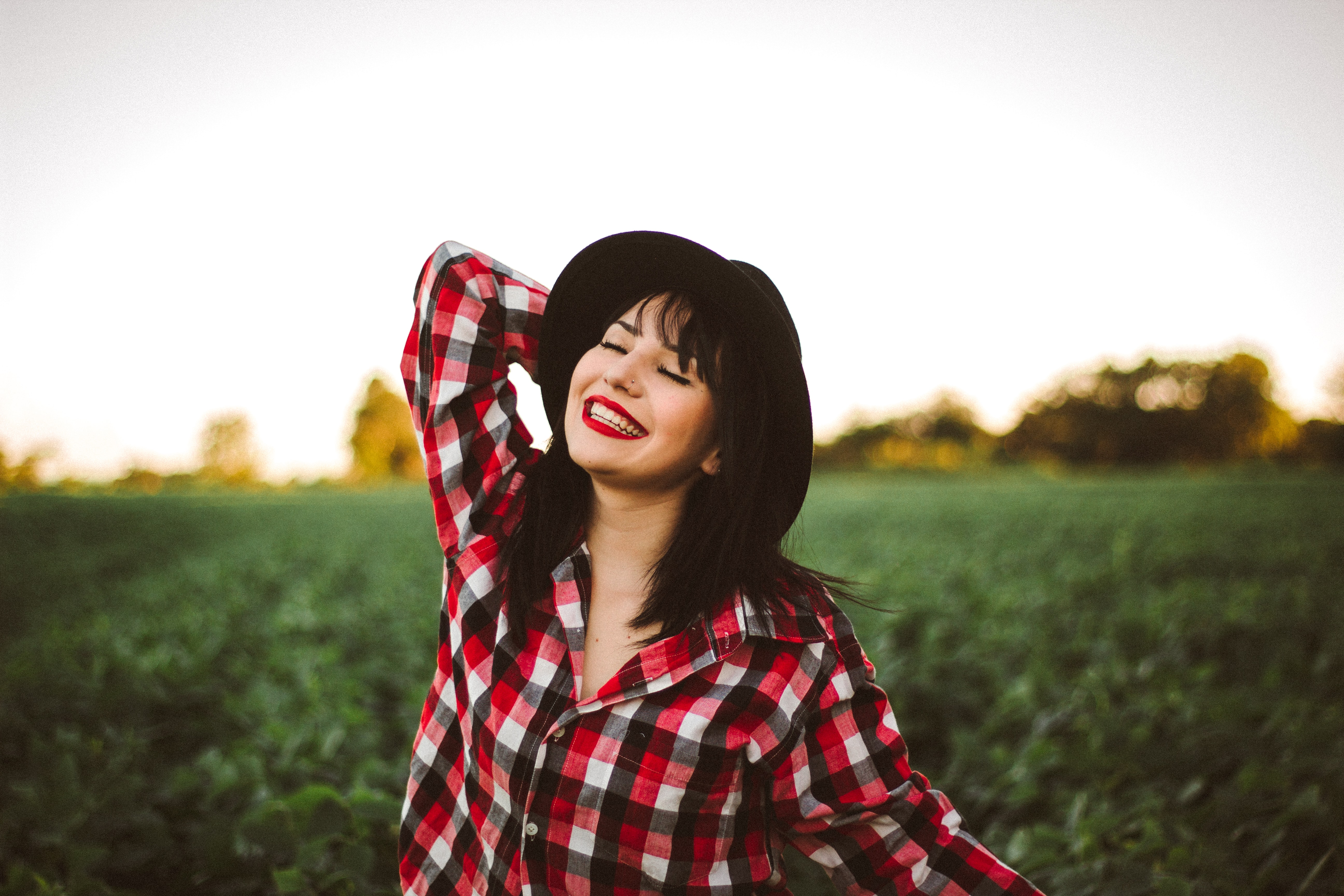 An Asian woman in a plaid shirt and black hat, posing for a picture in a field.