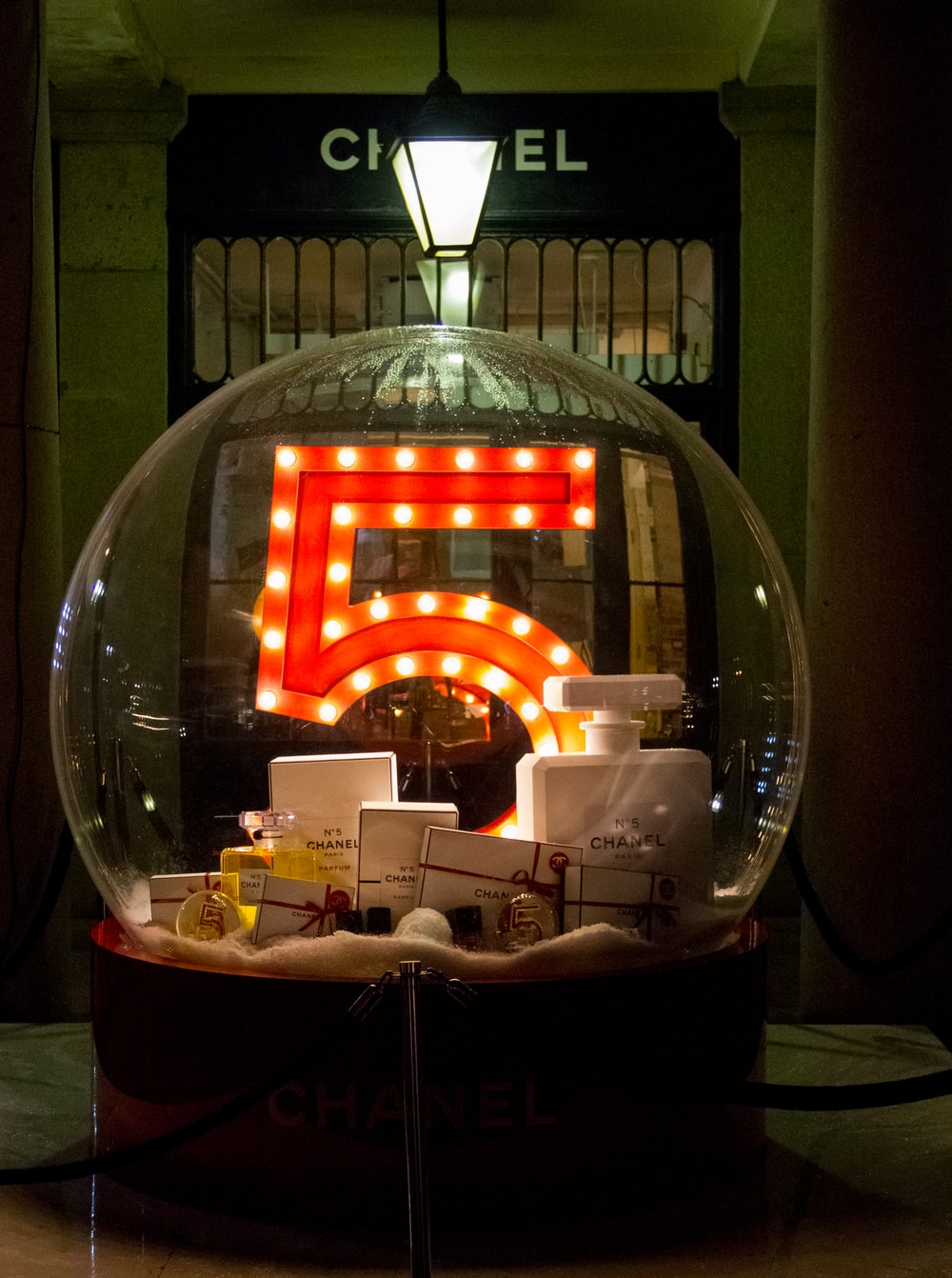 A large glass ball with the number 5, full of Chanel products in front of their storefront.