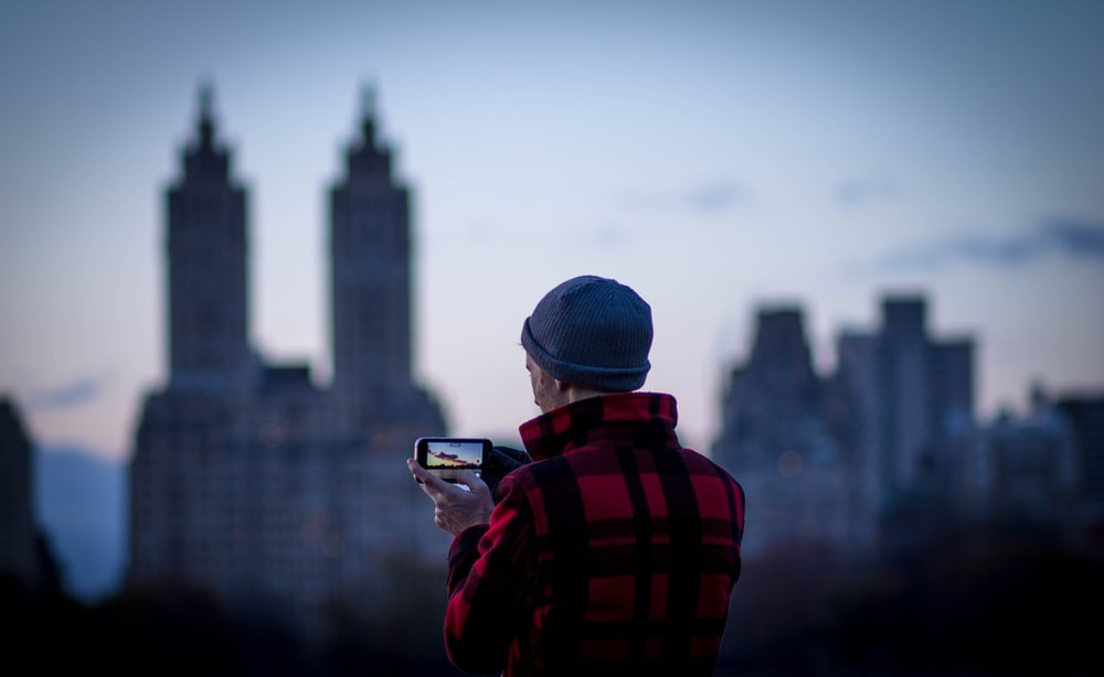 person taking a picture of city at daytime