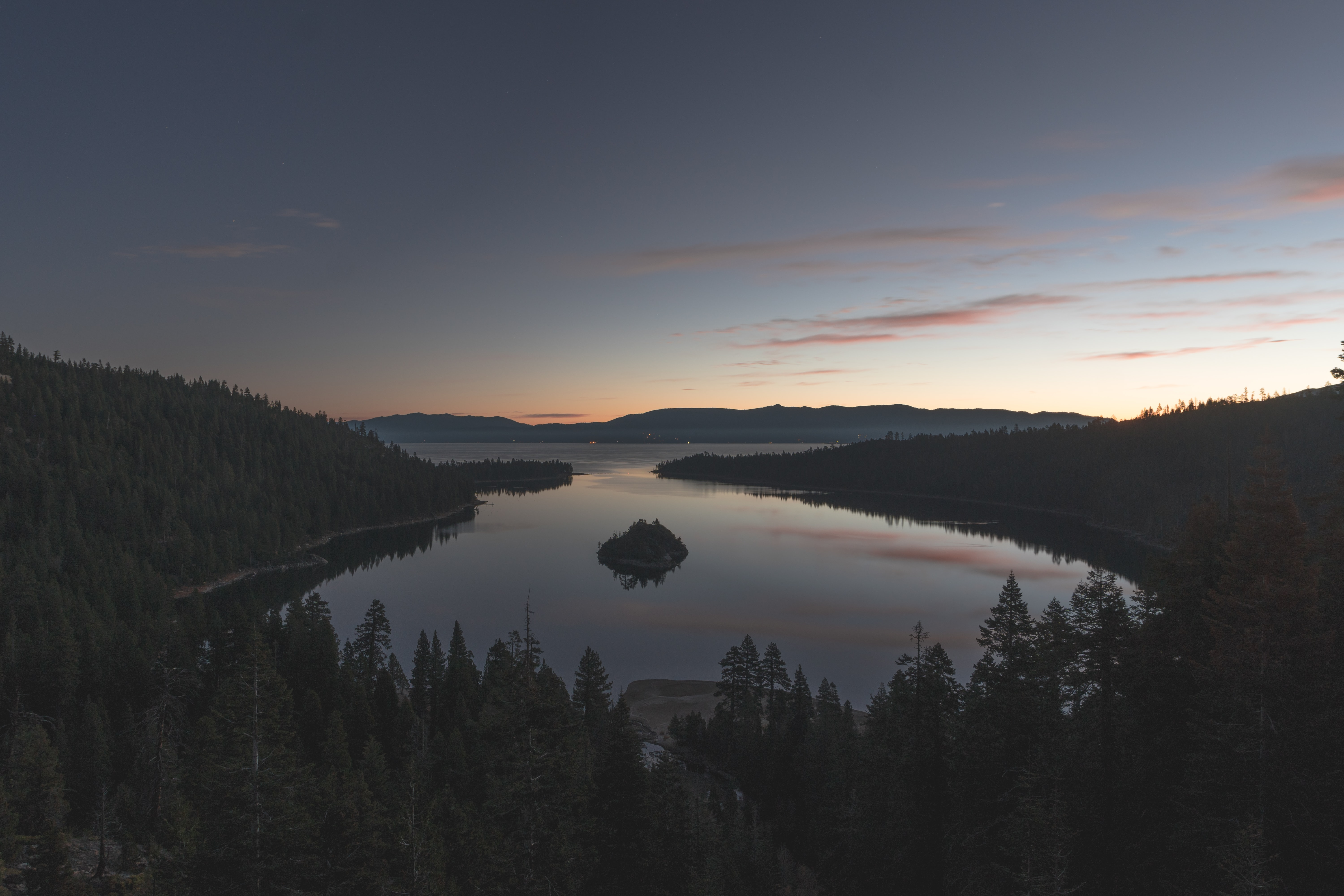 A calm lake situated in the forest of Emerald Bay, Lake Tahoe, reflecting the sunset on its waters