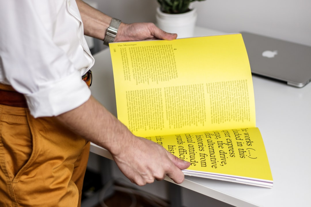 A man in a white shirt opening a book with yellow pages
