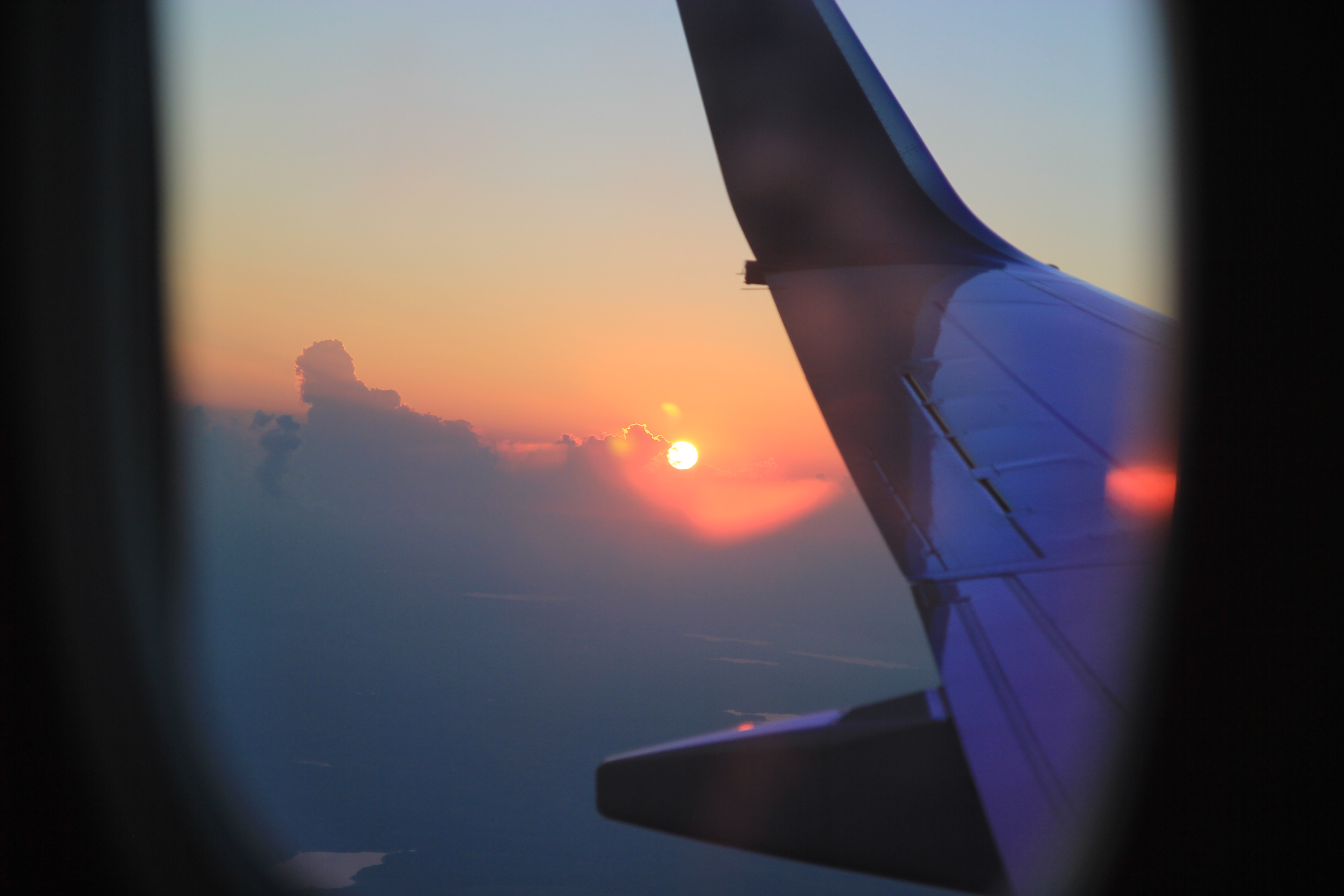 A passenger's view of the distance sunset from a plane window, with the plane's wing in the foreground