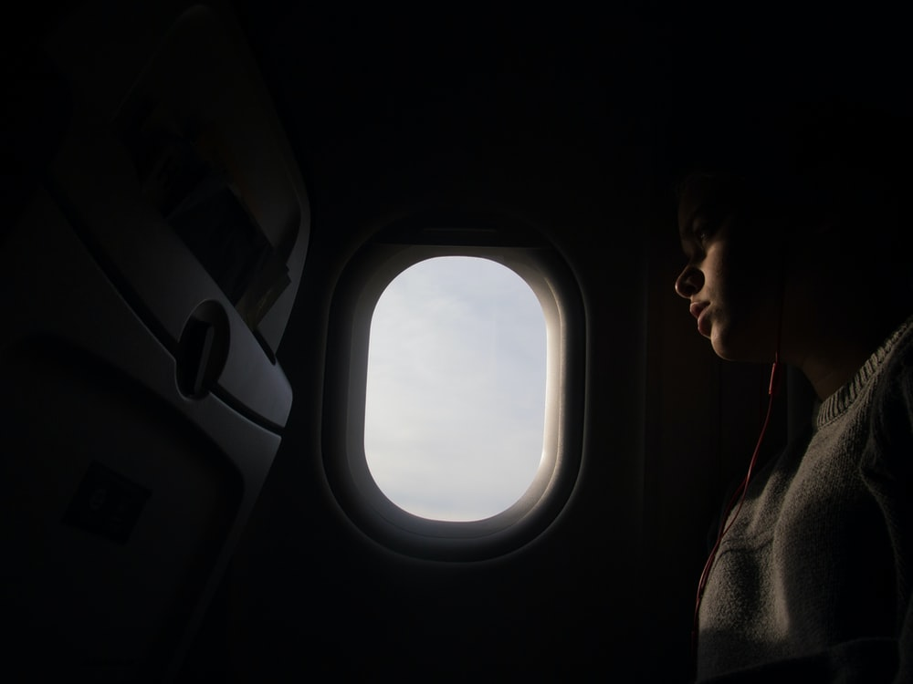 woman using red in-ear headphones while riding airplane