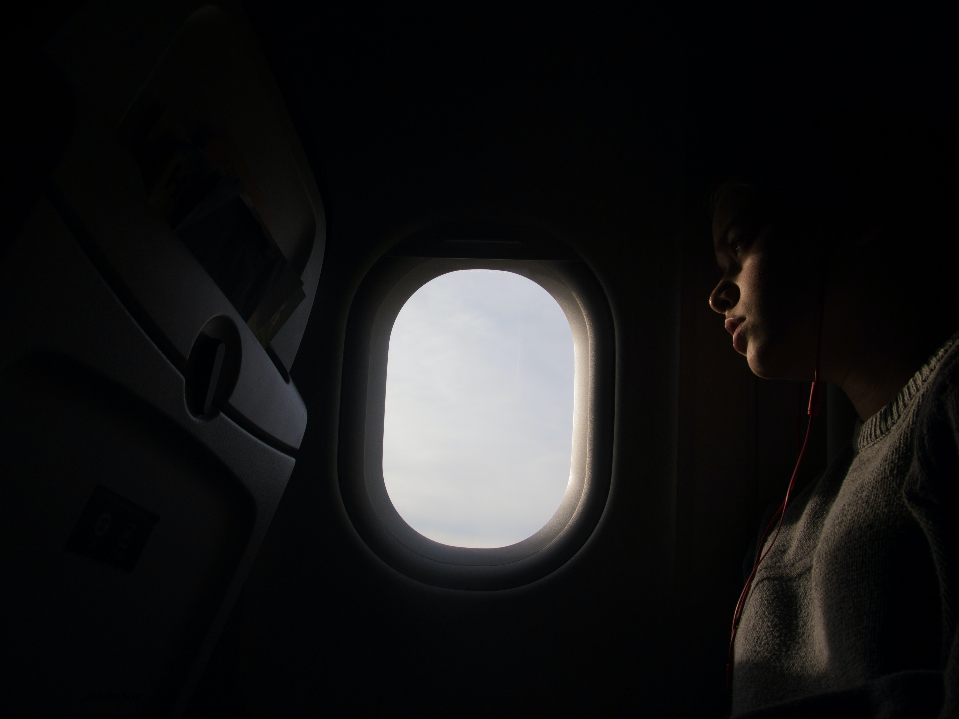 A dim shot of a person sitting next to an oval airplane window