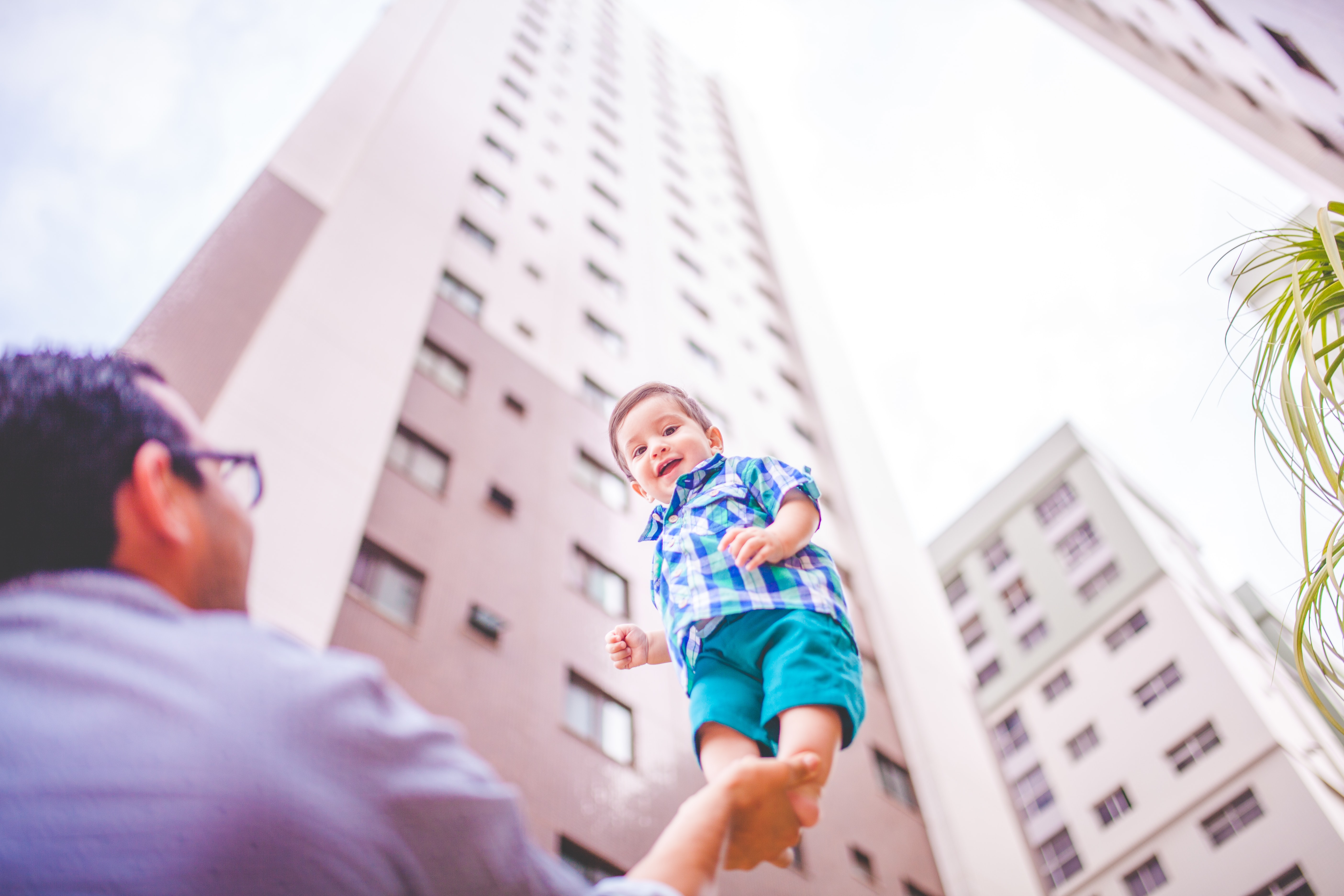 A man holds a child on the palm of his hand in front of a skyscraper