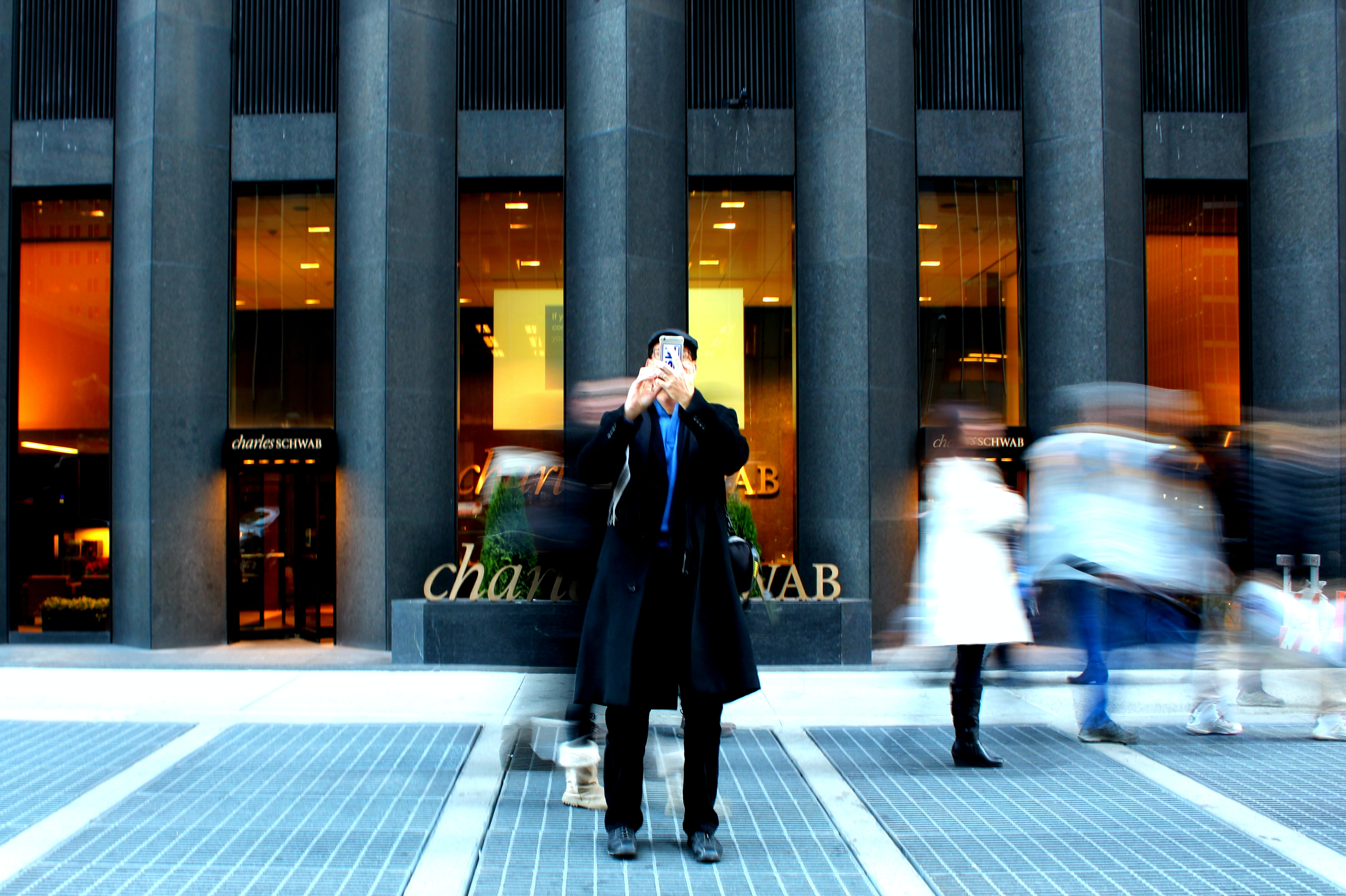 A man takes a photo facing the camera in front of the Charles Schwab Bank.